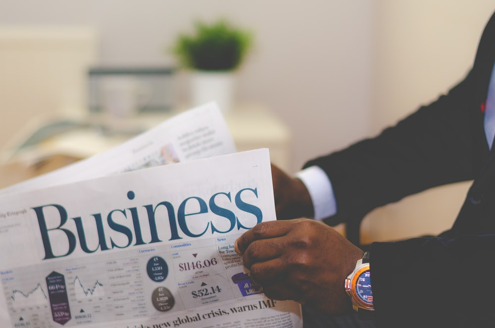 person wearing suit reading business newspaper