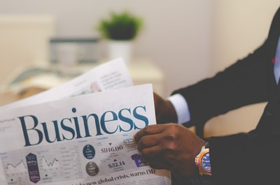 person wearing suit reading business newspaper business teams background