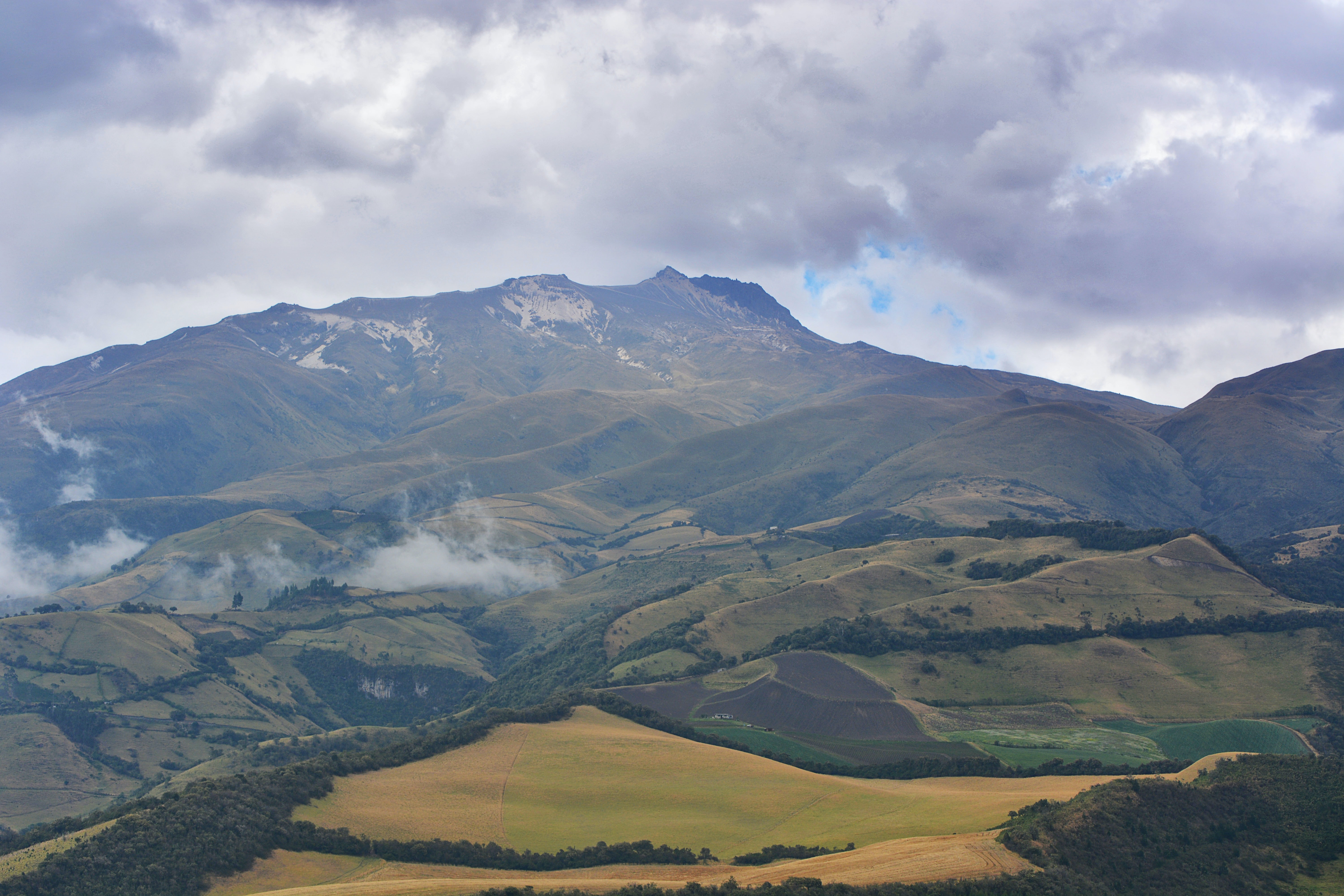 A patchwork of fields and forests at the foot of a mountain in Quito