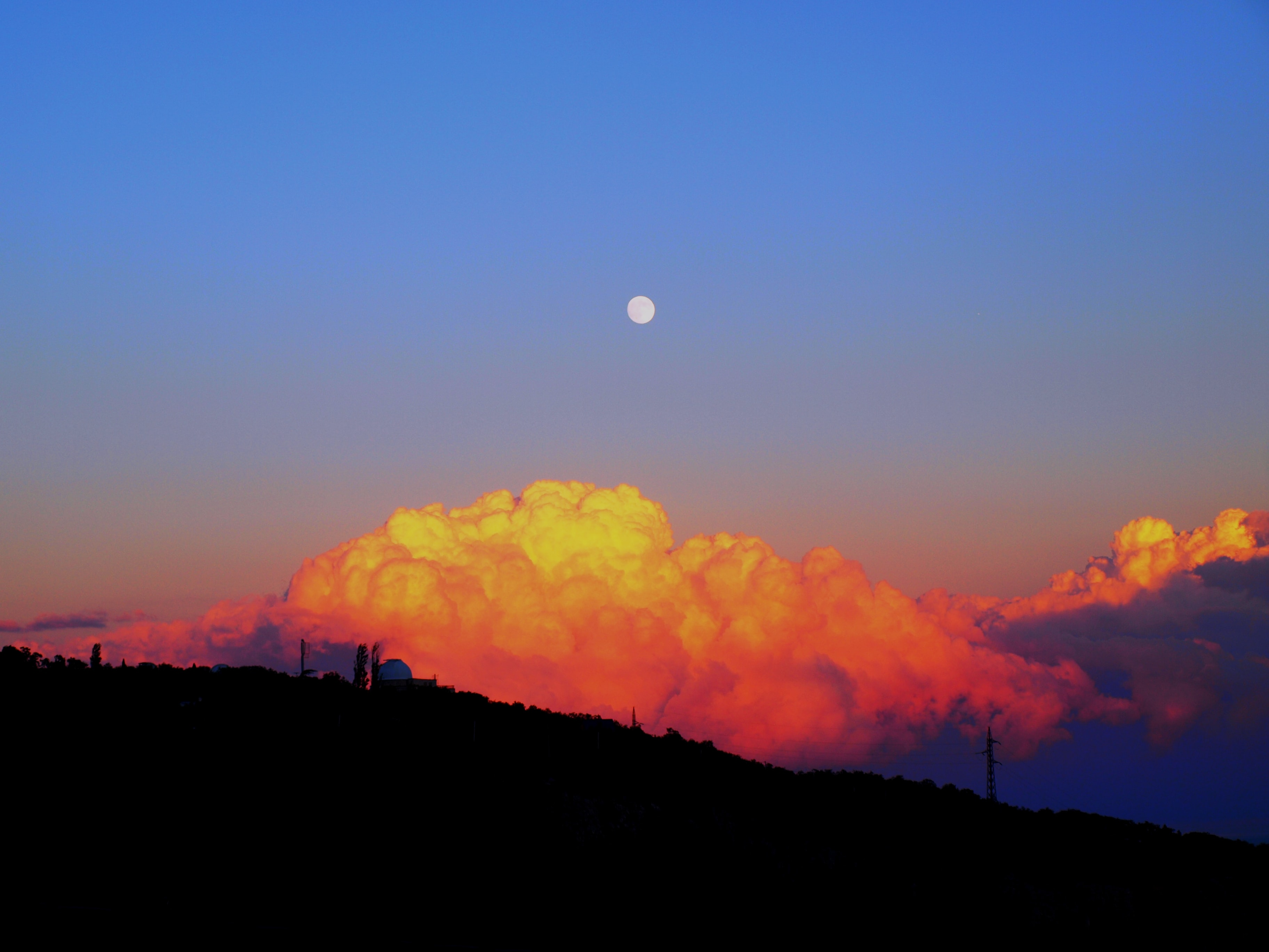 Full moon rises over puffy orange clouds during sunset in Крым