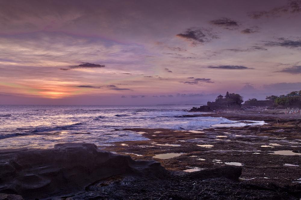 blue sea hitting seashore during golden hour