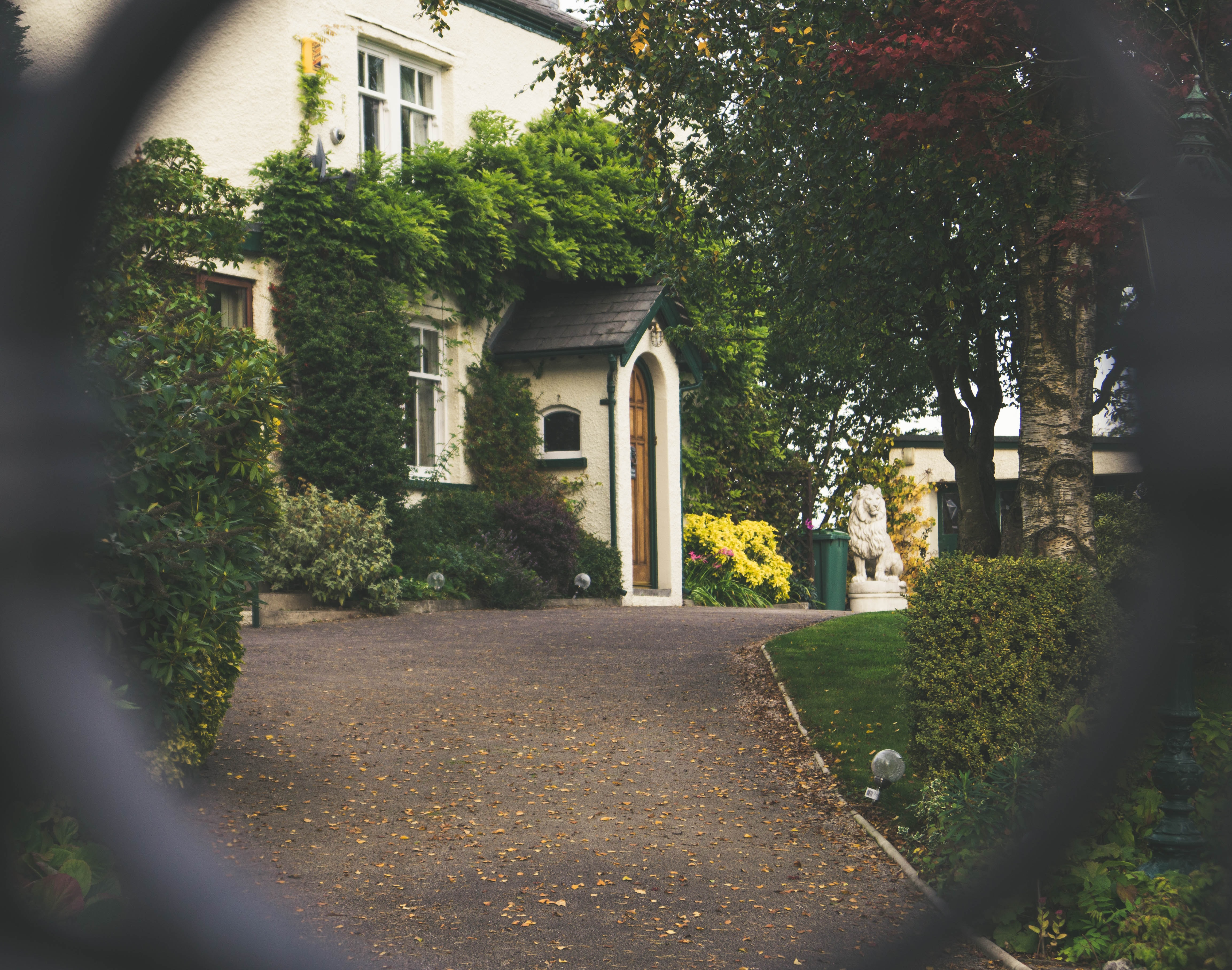 The entrance to a mansion with a beautiful garden seen through the fence