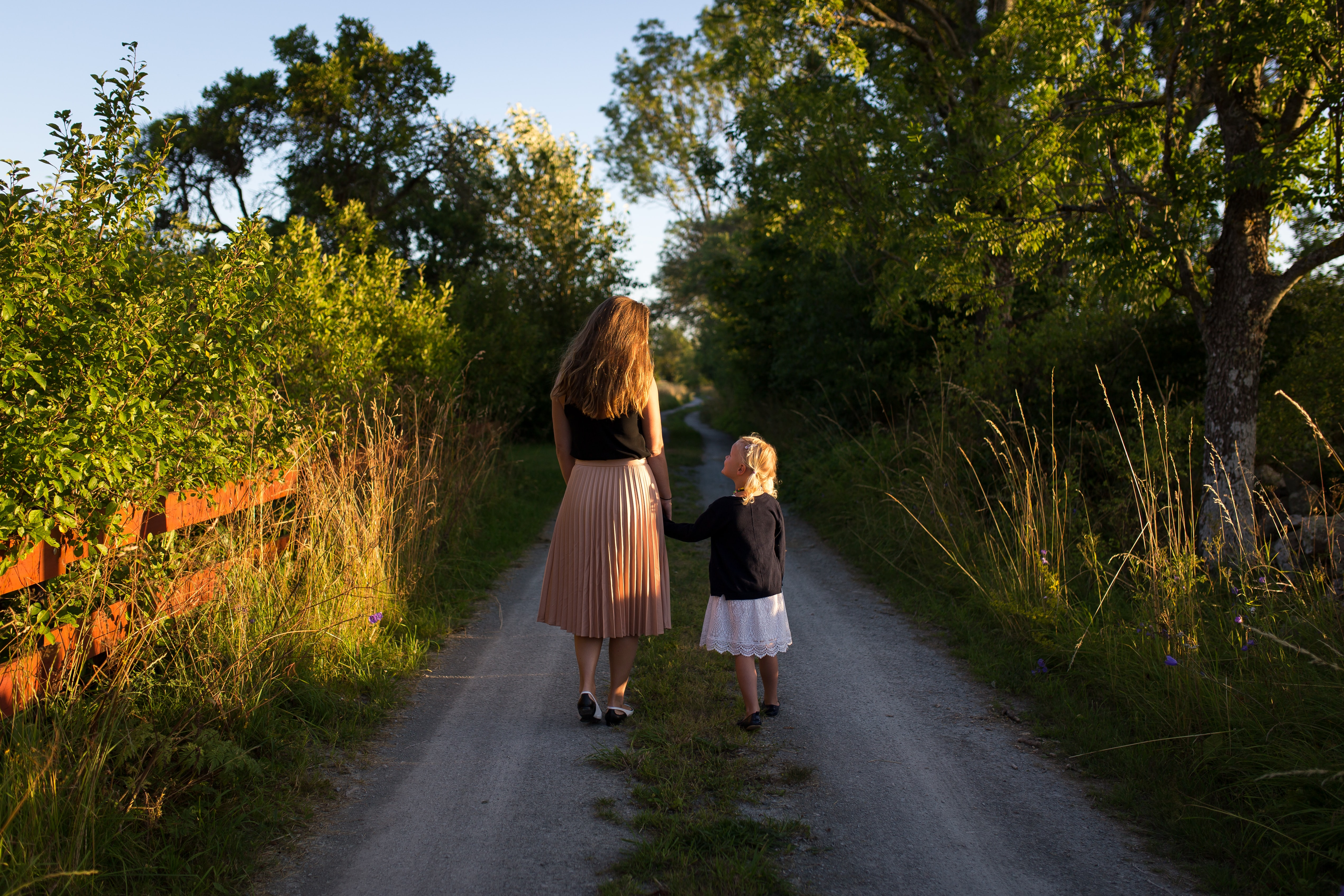 Child and mother walk through park trail as shadows lengthen