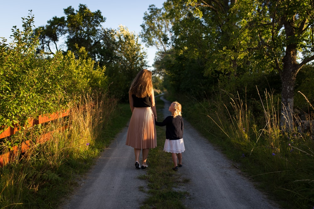 woman and girl walking on road surrounded by green grass