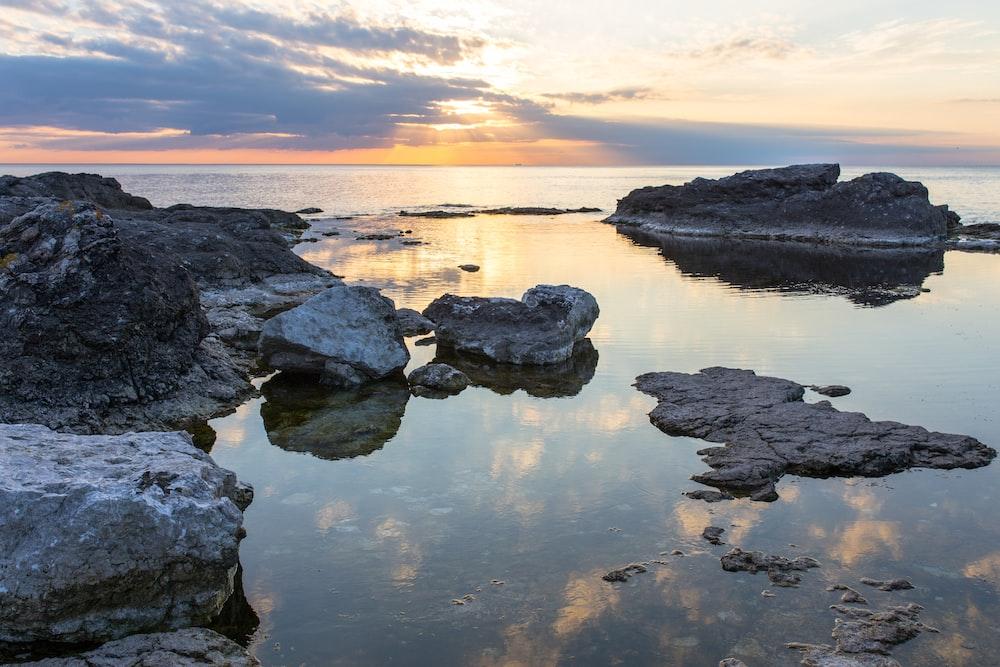 rocks on body of water under cloudy sky