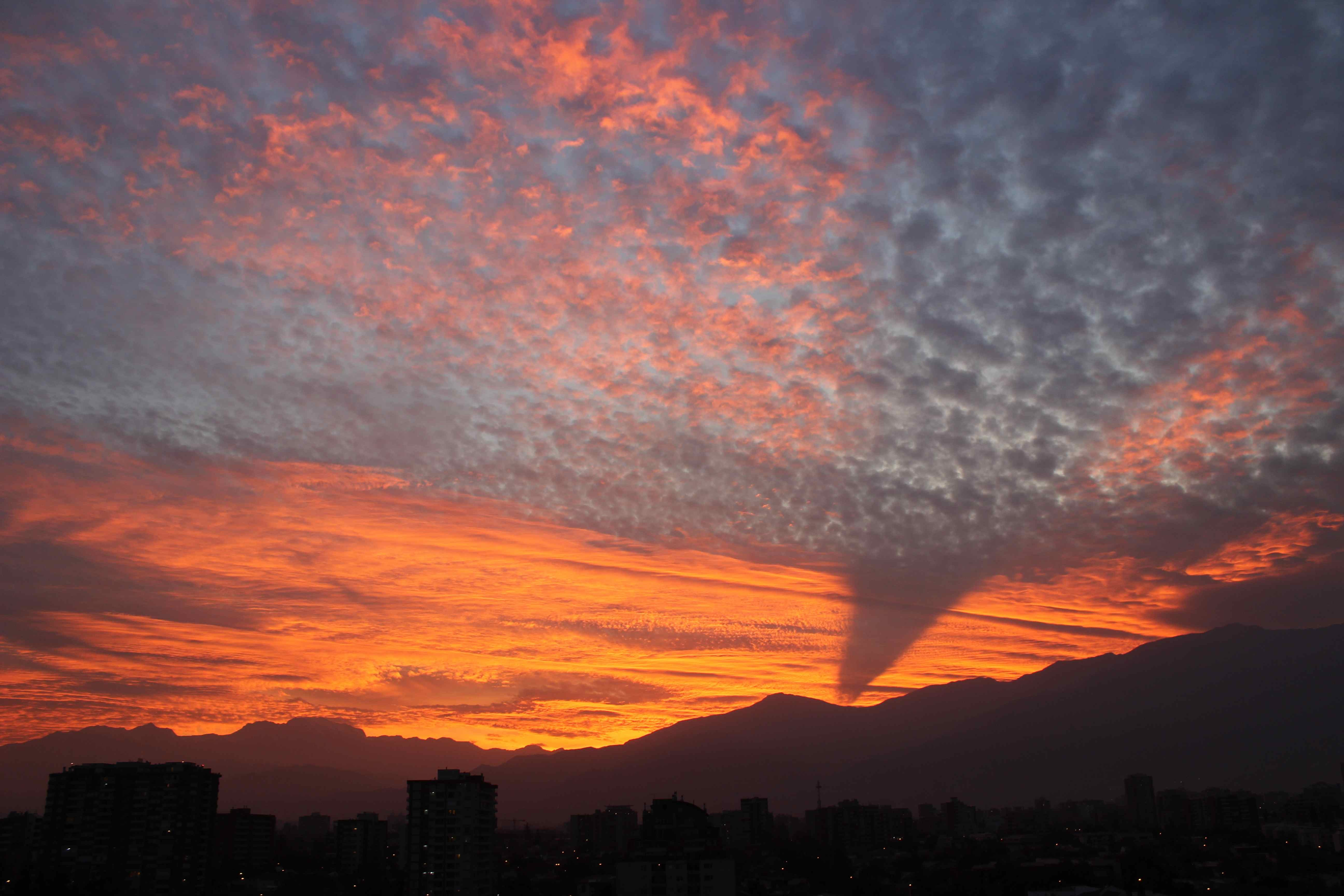 Moody sunset in Santiago with deep orange and cloudscape.