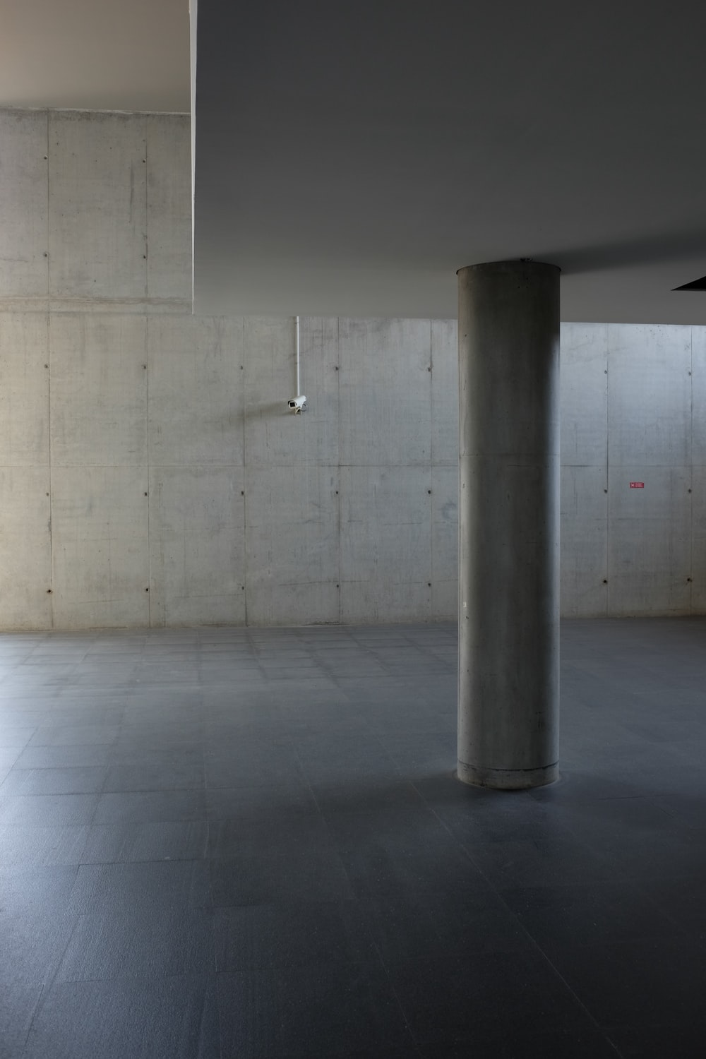 The inside of a building made of concrete walls with a platform supported by pillars.