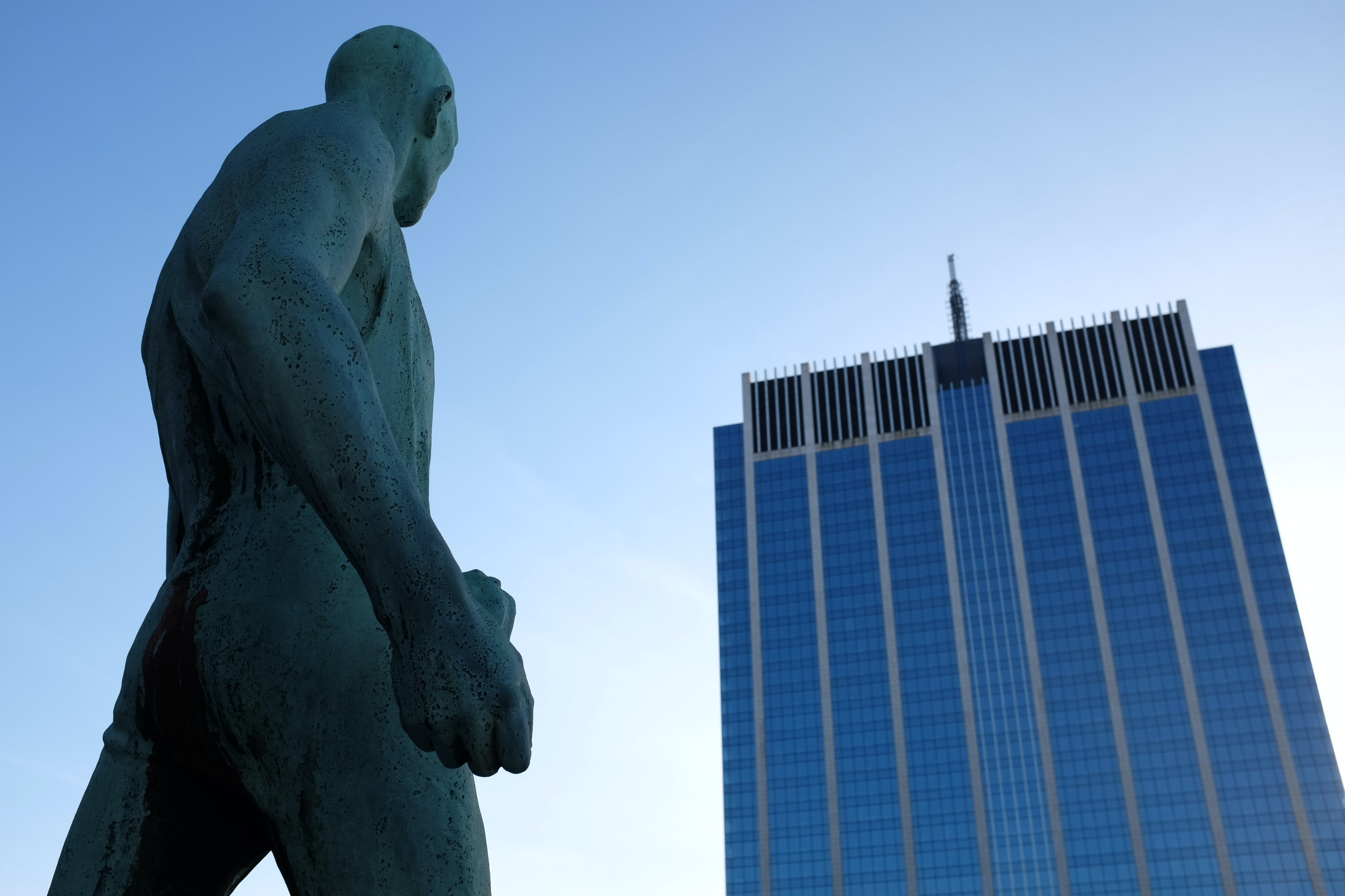 Statue of muscular naked man looking at corporate skyscraper in Bruxelles