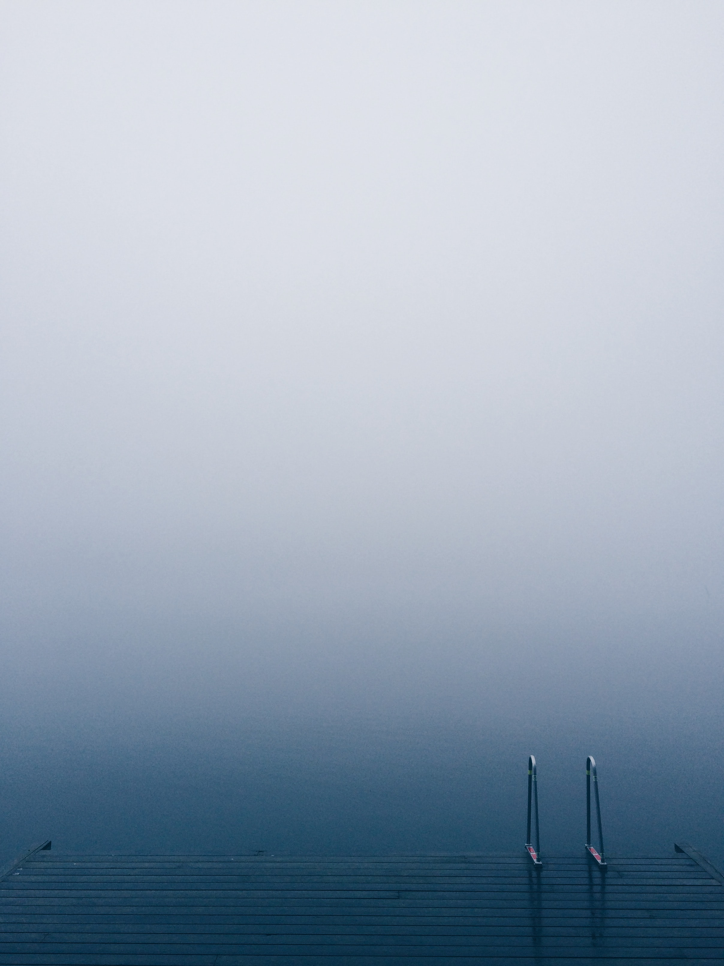 Lake pier with a ladder on serene waters on a foggy day