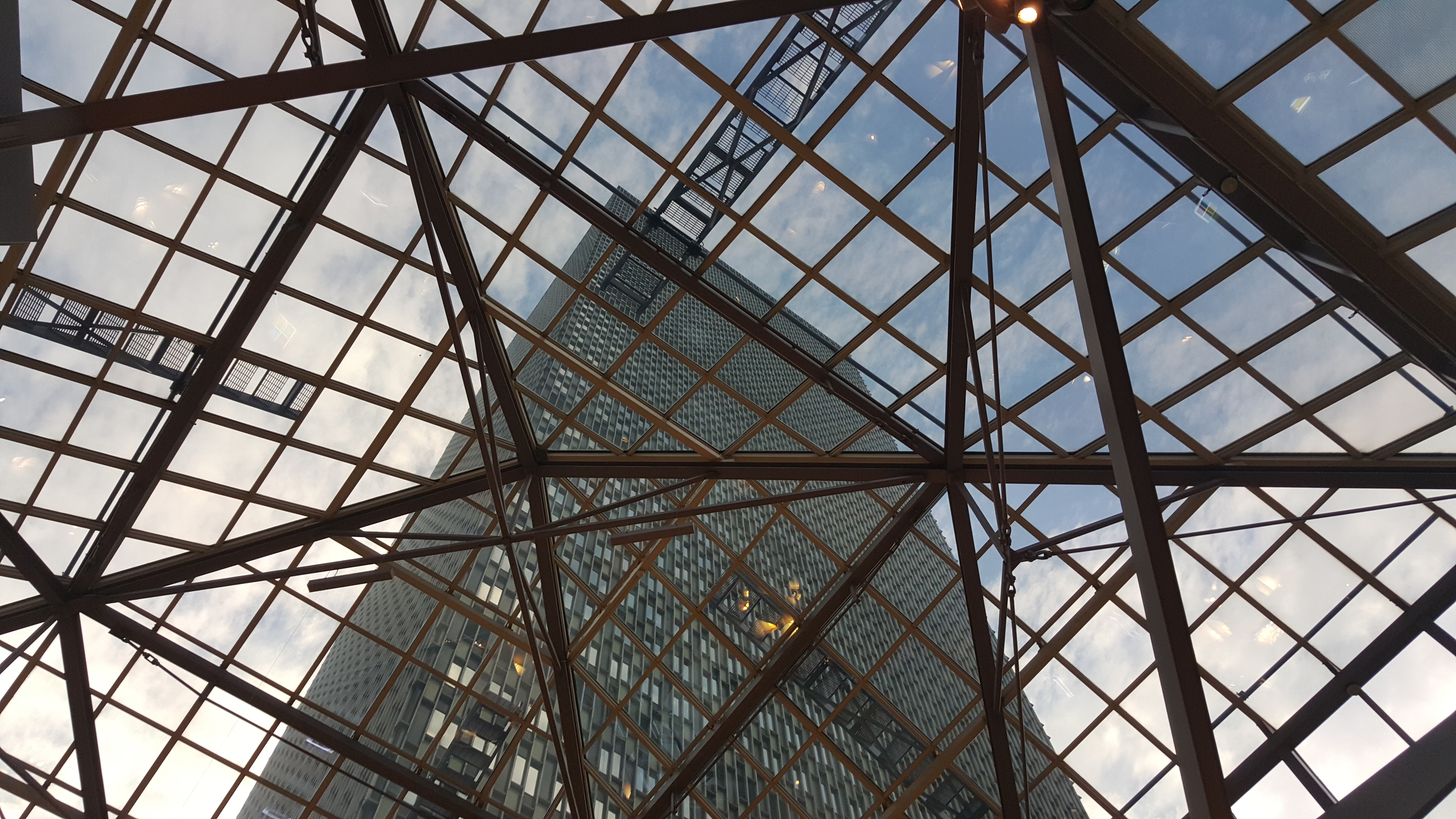 Steel support beams in a glass ceiling with a view on a high-rise outside