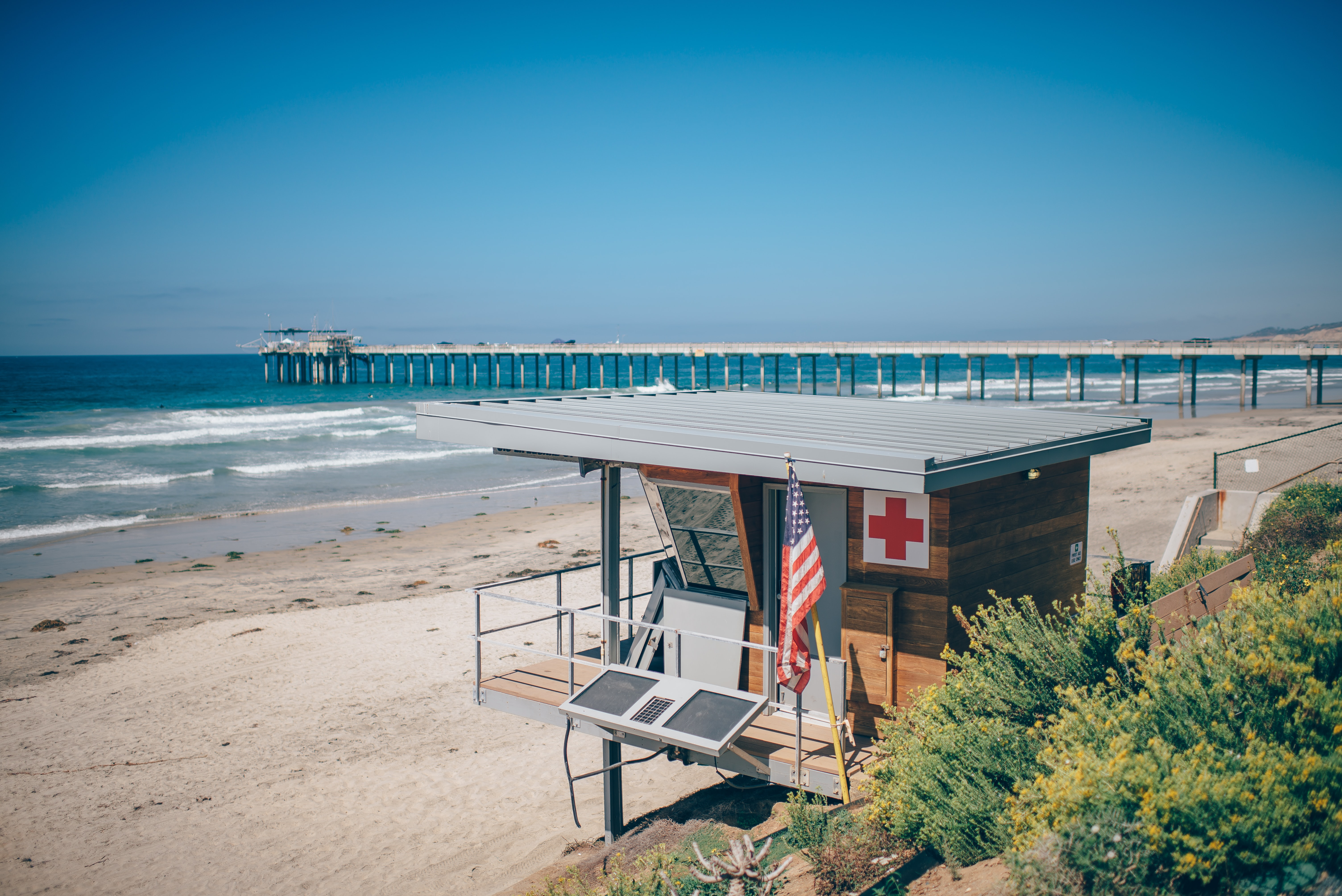 Exquisite lifeguard quarters at beach in an ocean with a boardwalk leading up to pier