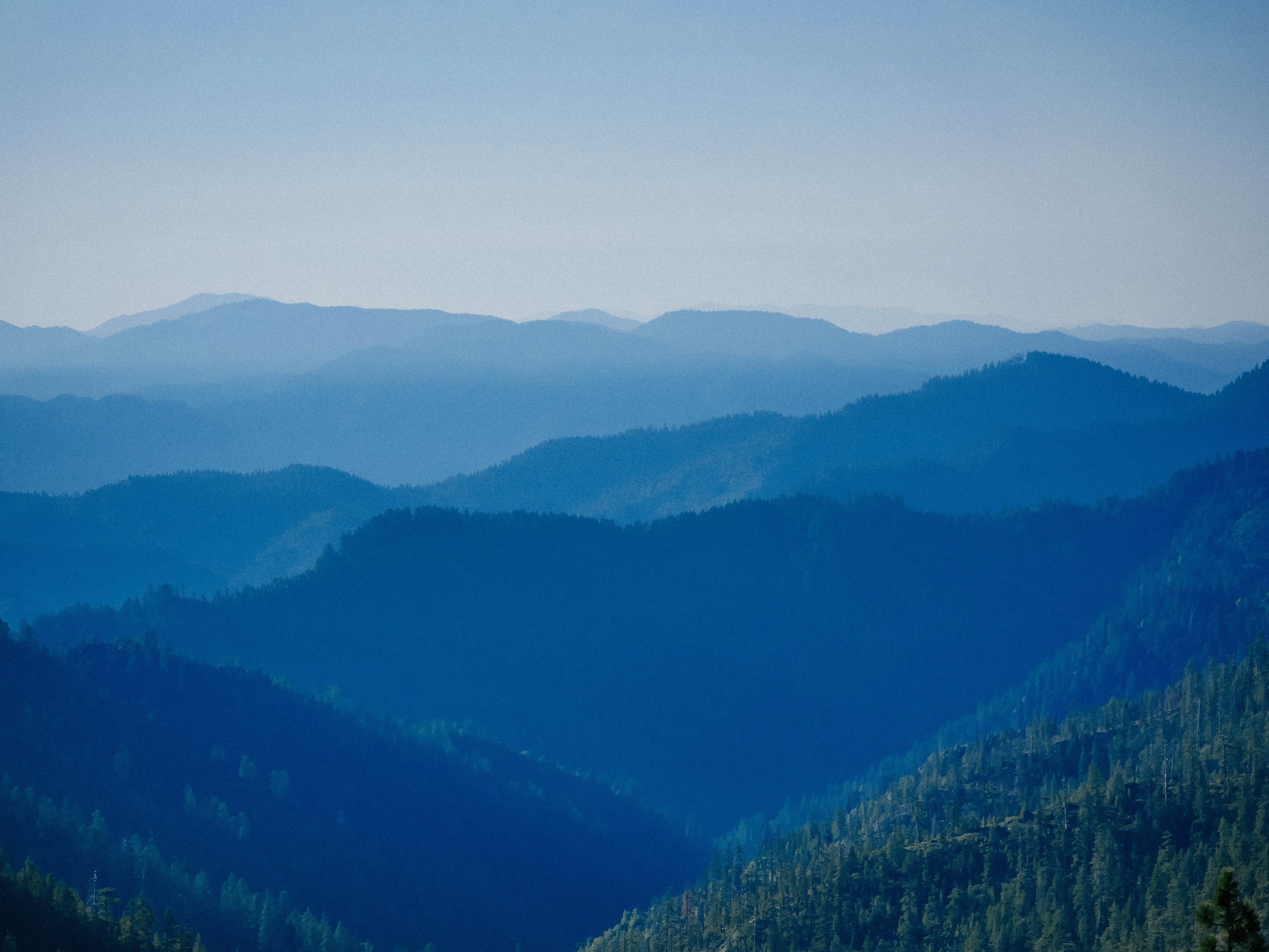 Wooded mountain ridges stretching to the horizon in the early morning
