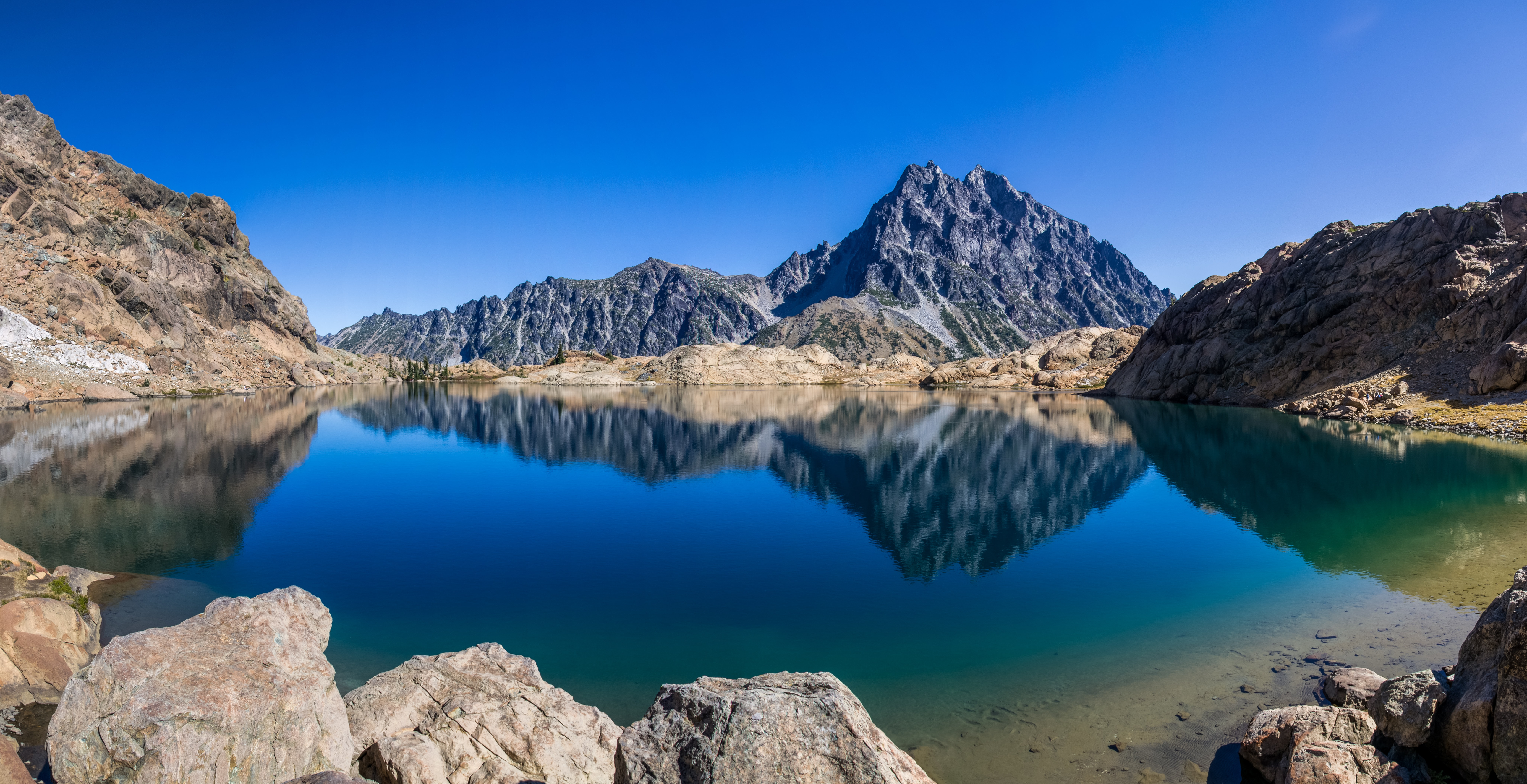 Jagged mountains reflected on the surface of a clear mountain lake