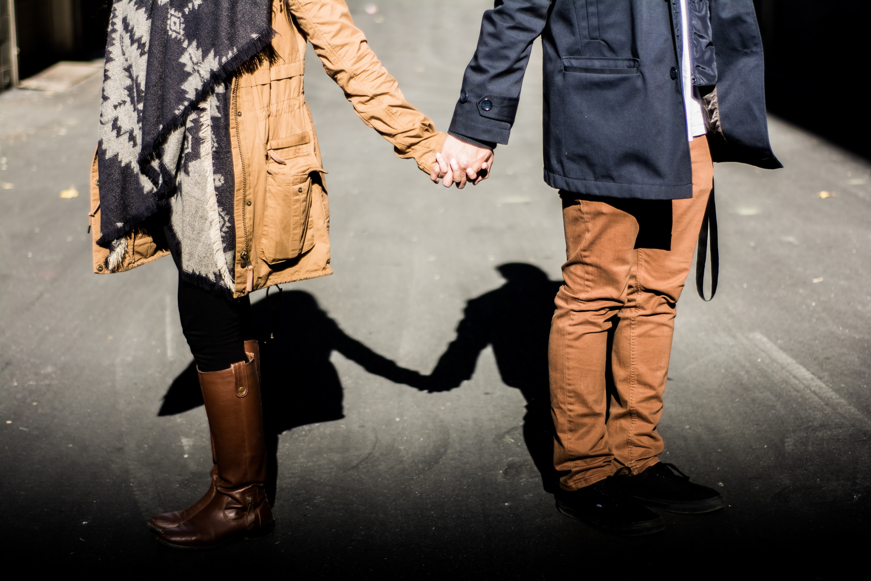 A couple in casual fall clothing holds hands in Edmonton, their shadow visible behind them