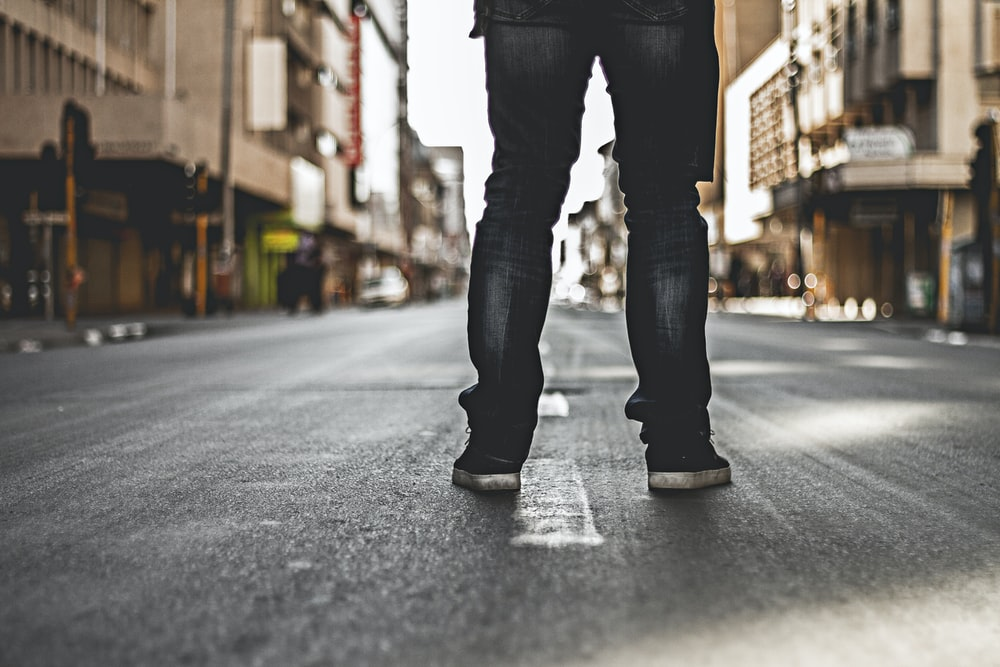 selective focus photography of person standing on blacktop road between buildings