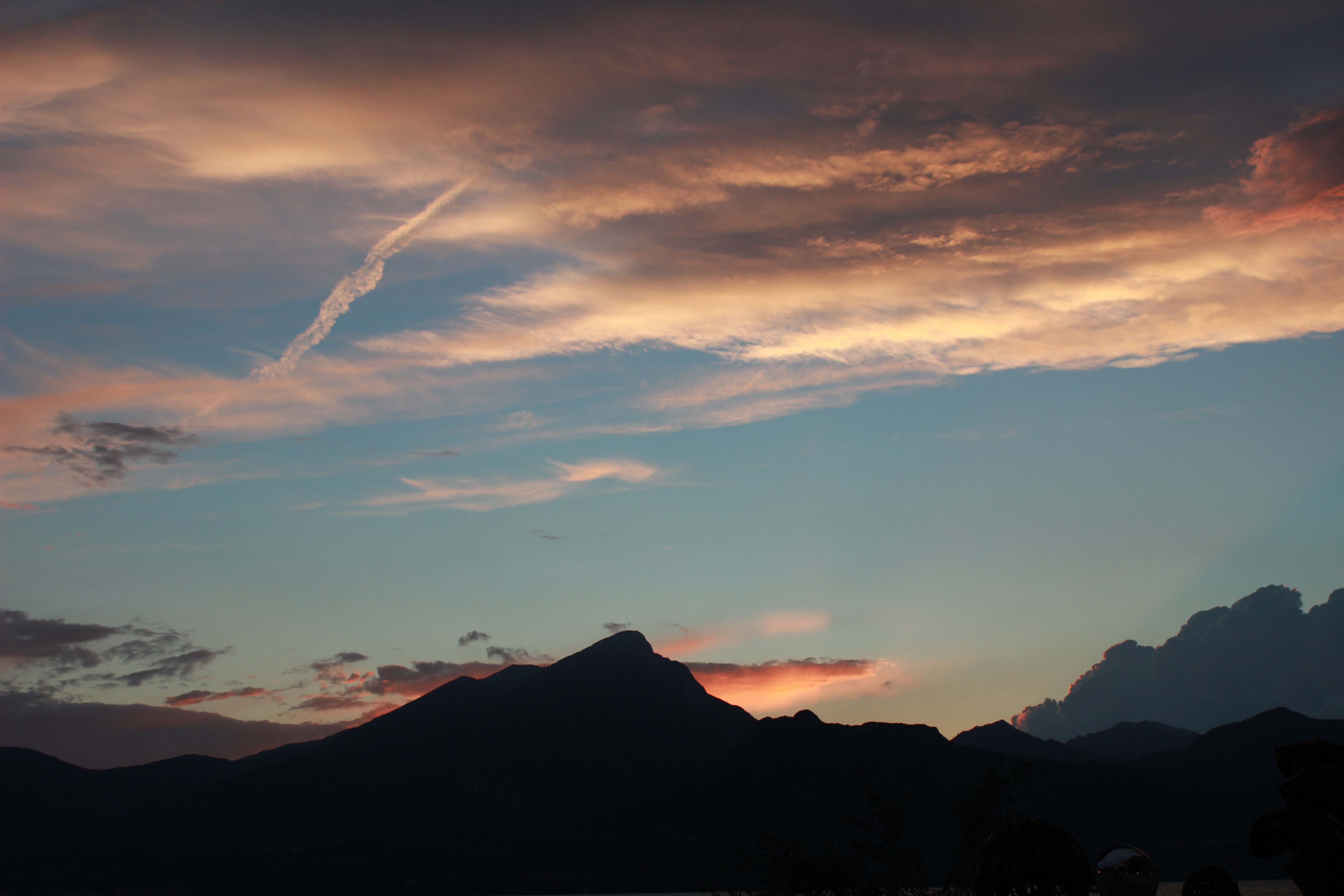 Mountains silhouetted against an evening sky with scattered clouds