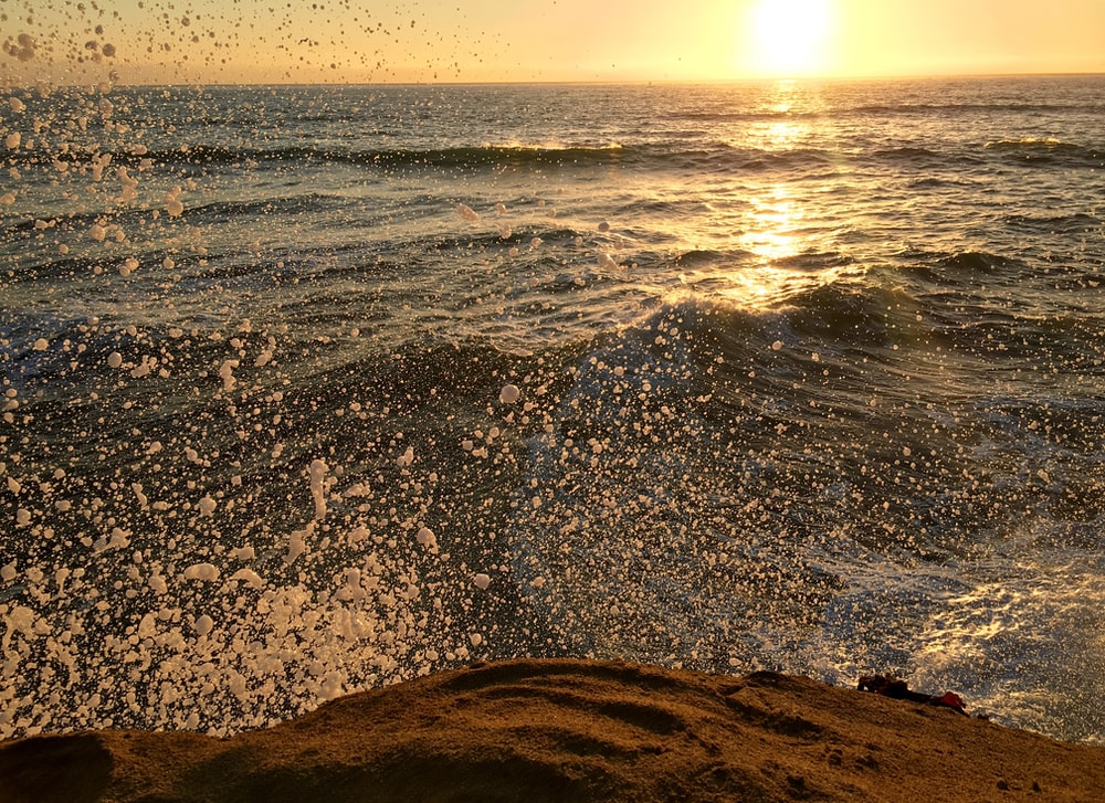 time lapse photography of sea wave splash during golden hour