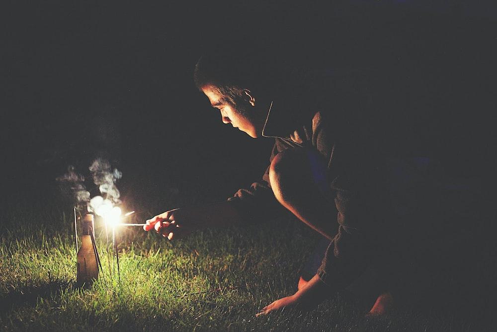man crouching holding sparkler
