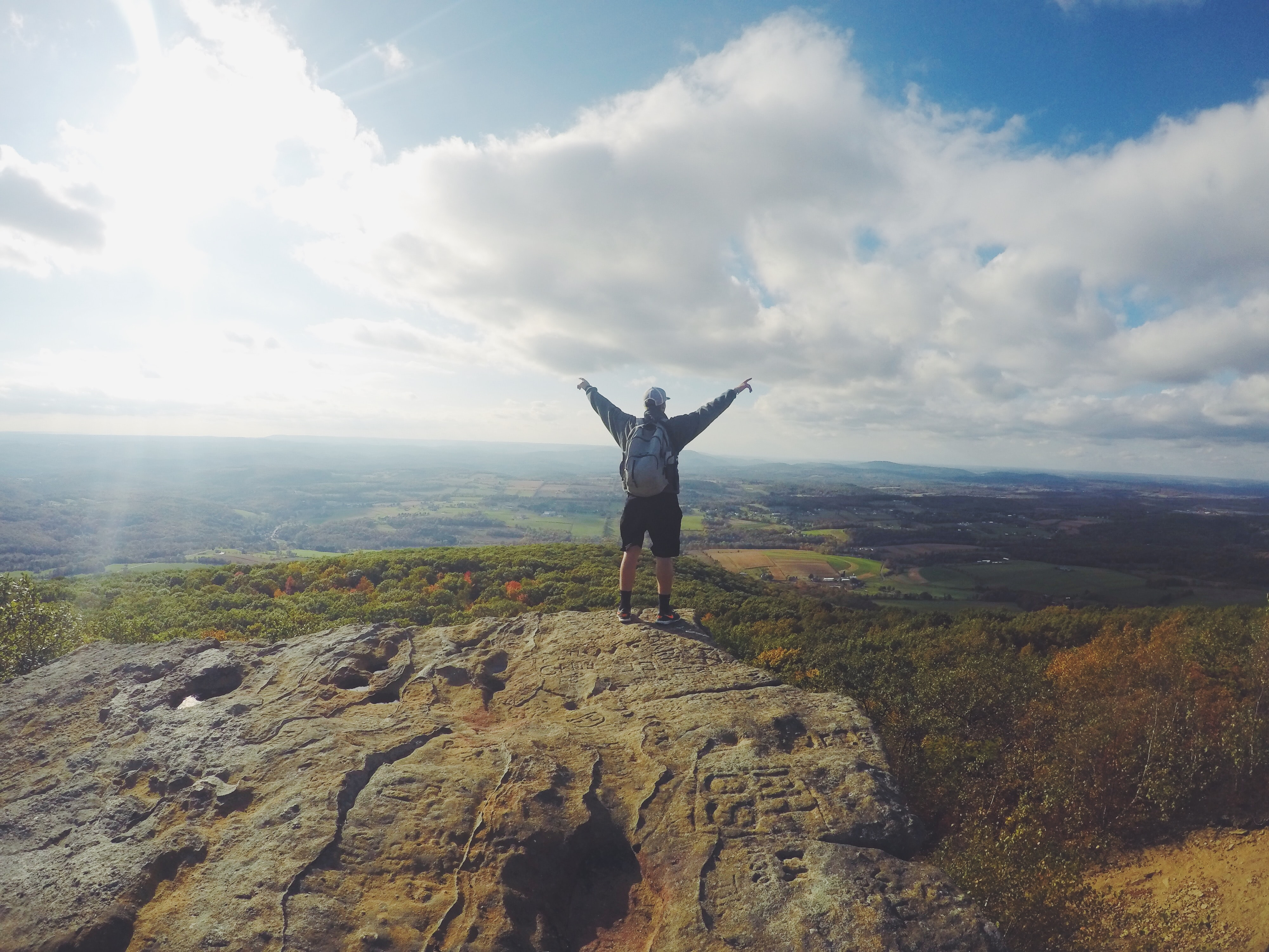 A man with a backpack standing with his hands outstretched on a rocky ledge overlooking green countryside