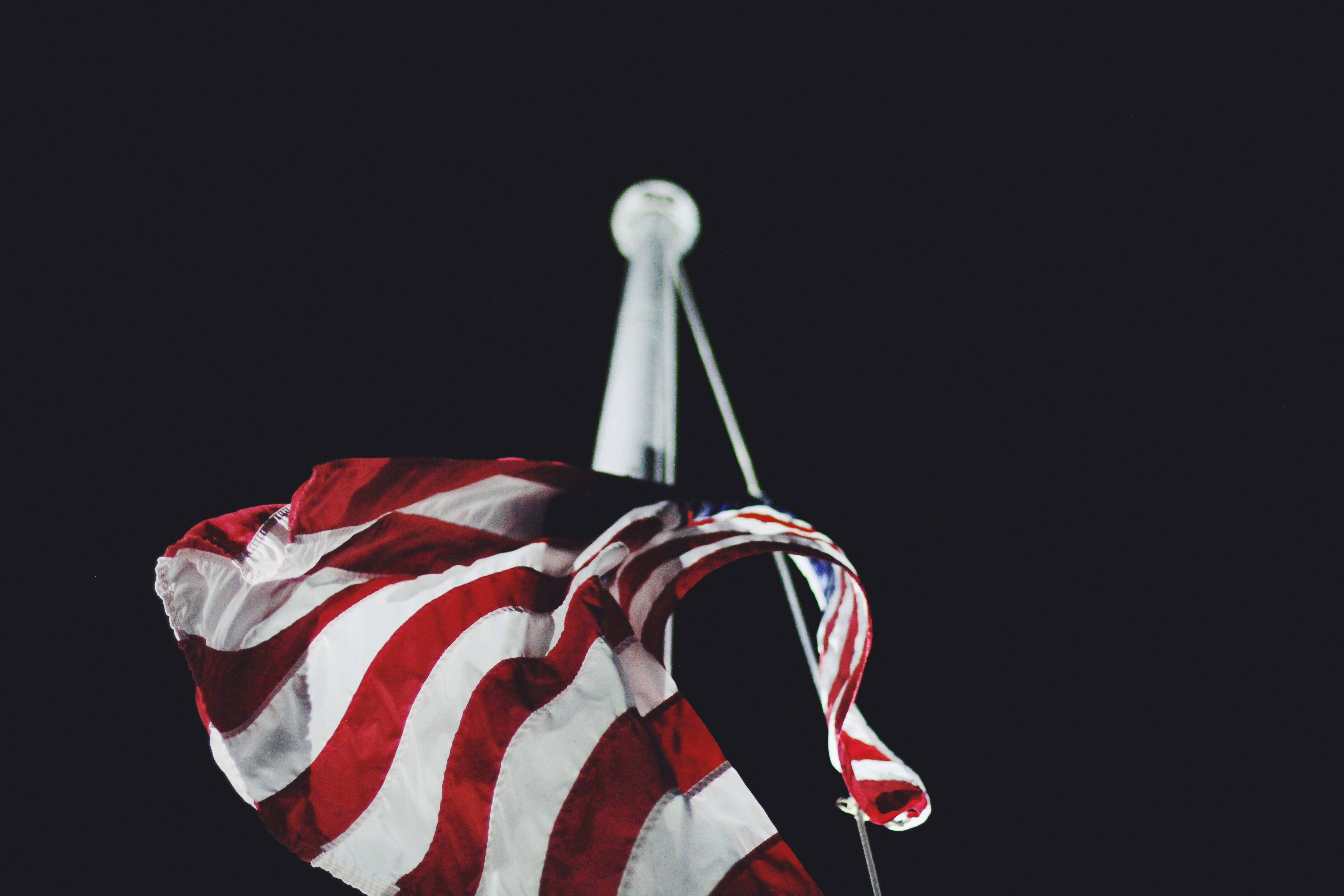 A close-up of the American flag on a flagpole.
