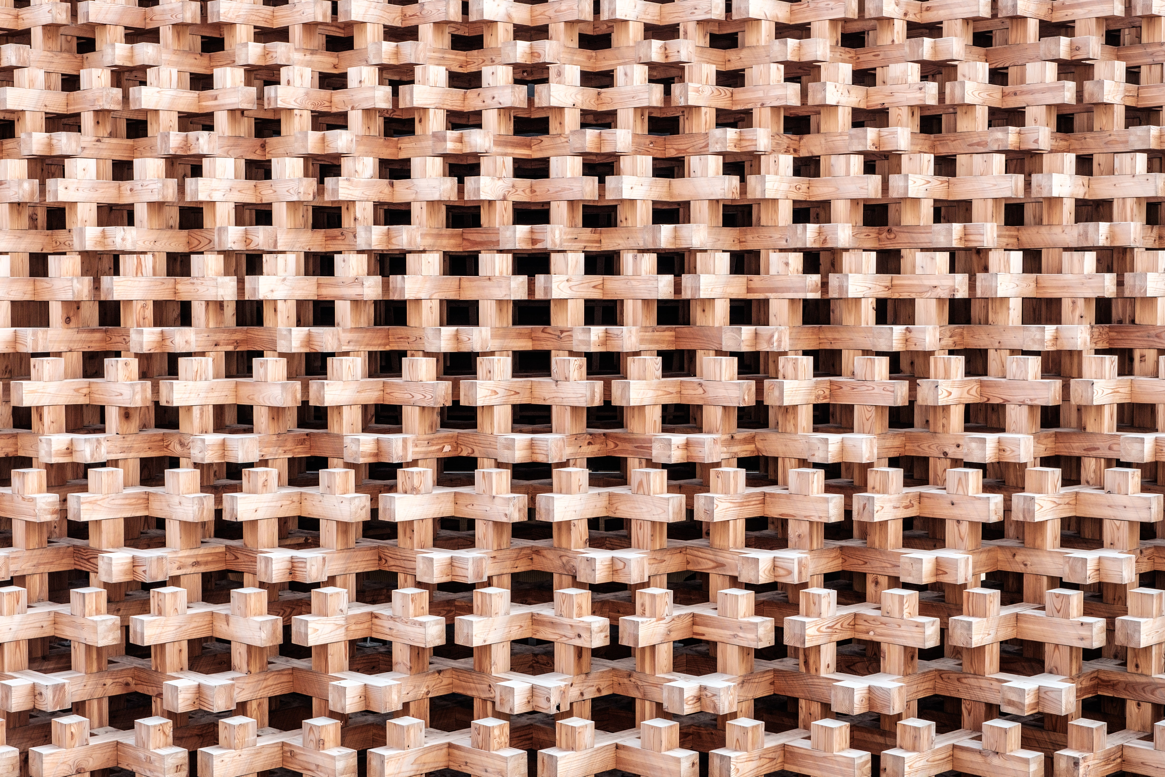A regular pattern made up of cross-shaped wooden blocks stacked up on top of each other