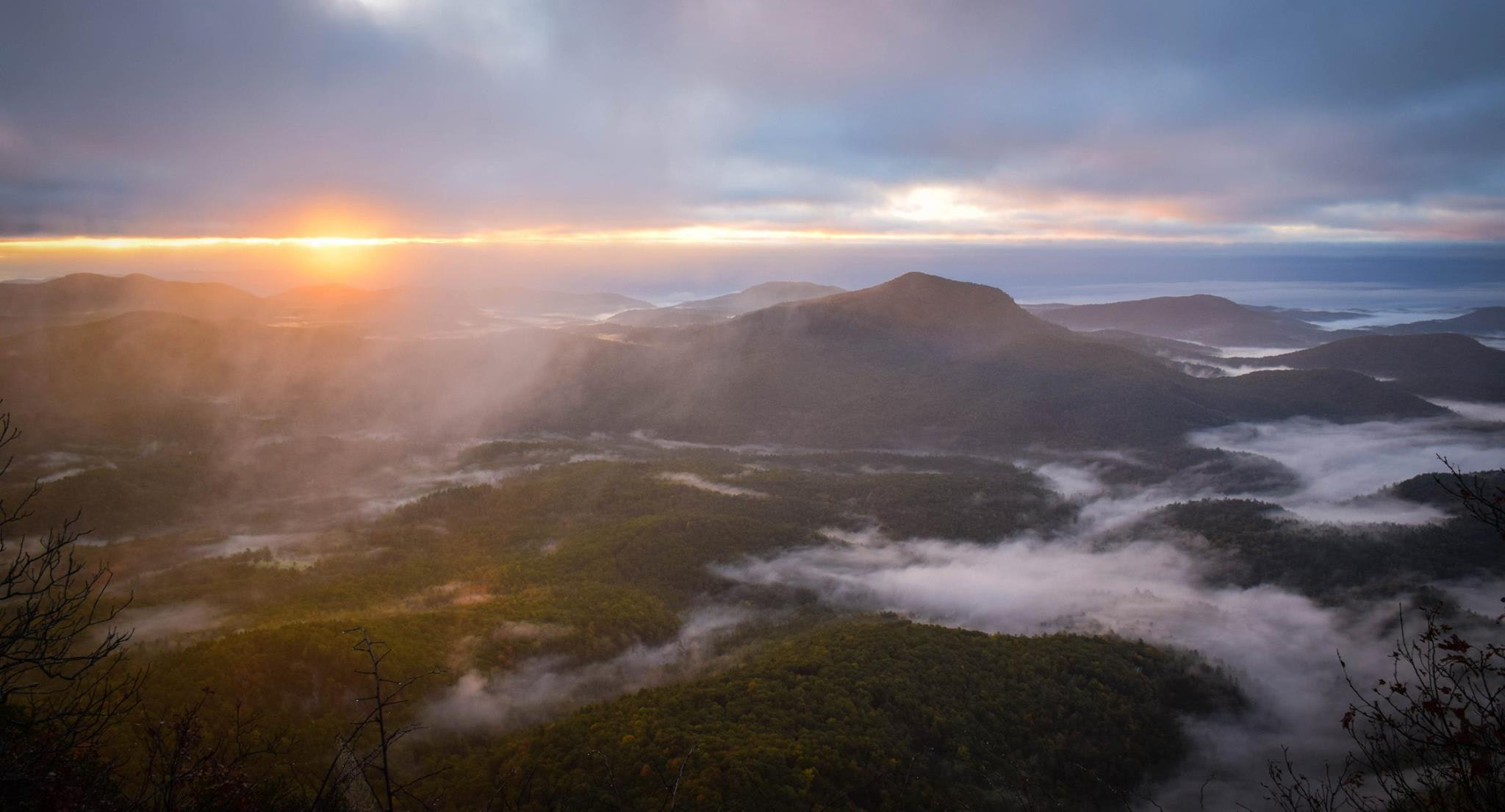 A high shot of mist over wooded mountain slopes during sunset