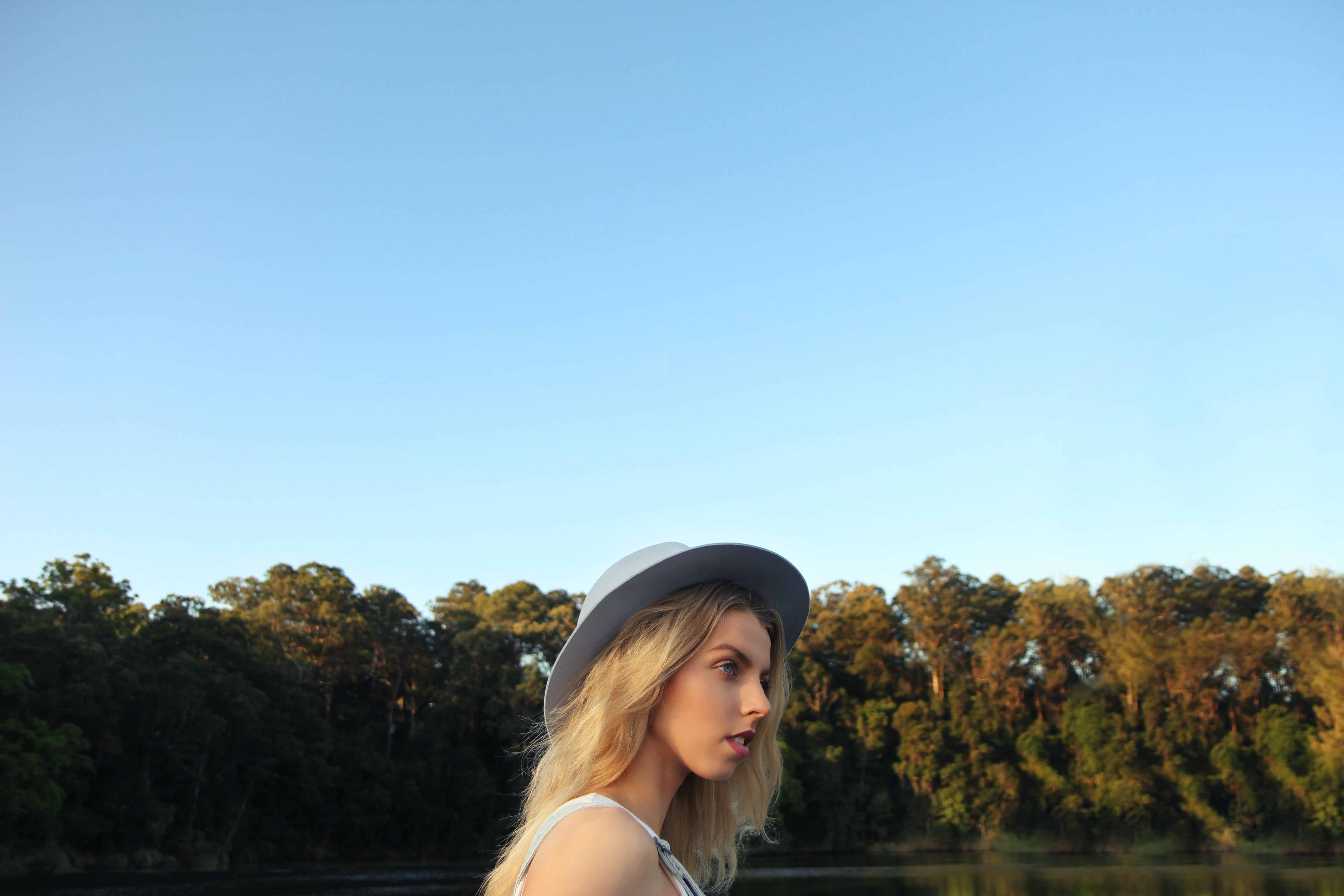 A young blonde woman in a hat near a forest under blue sky in Coomera