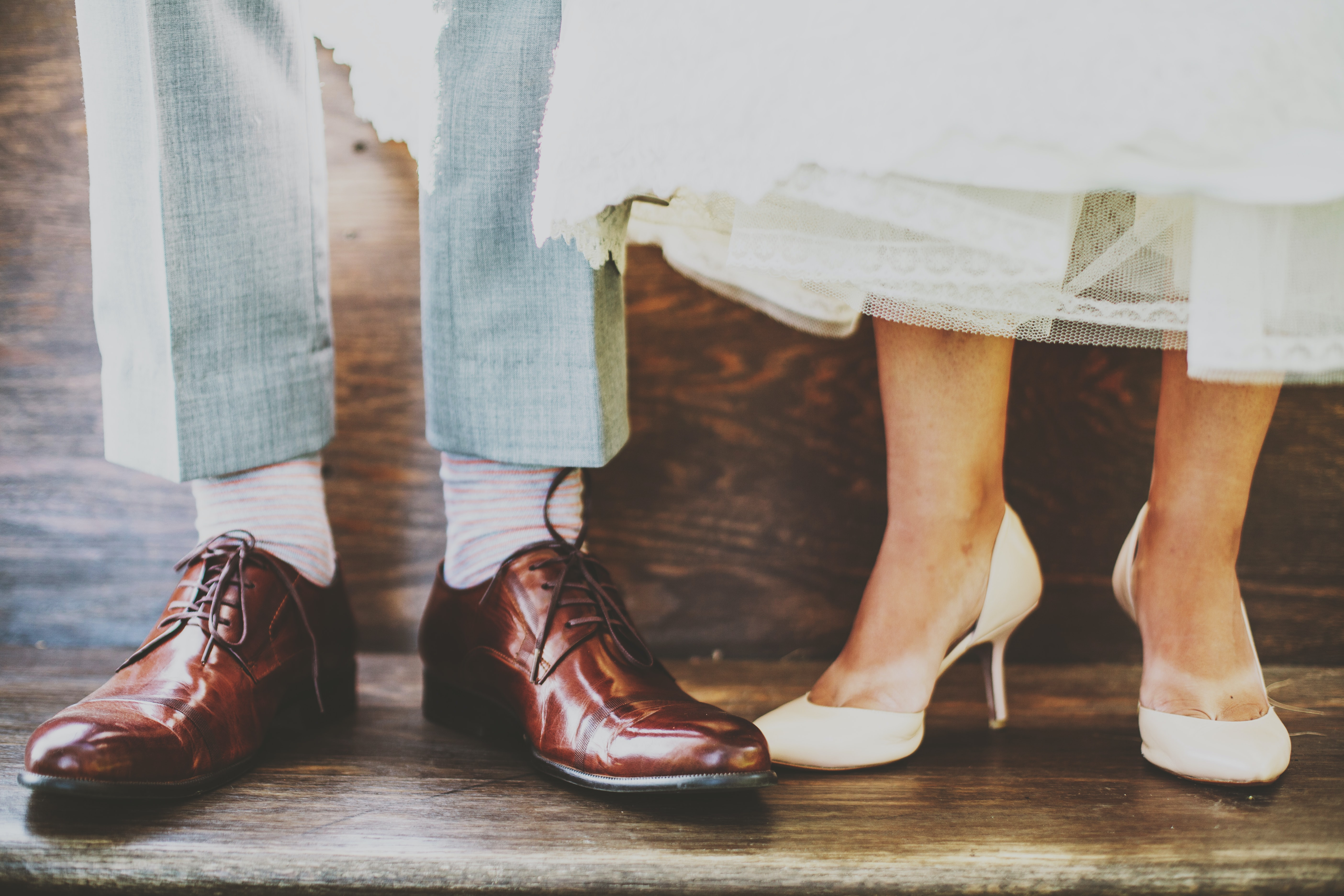 Shoes of a bride and groom illuminated under soft light