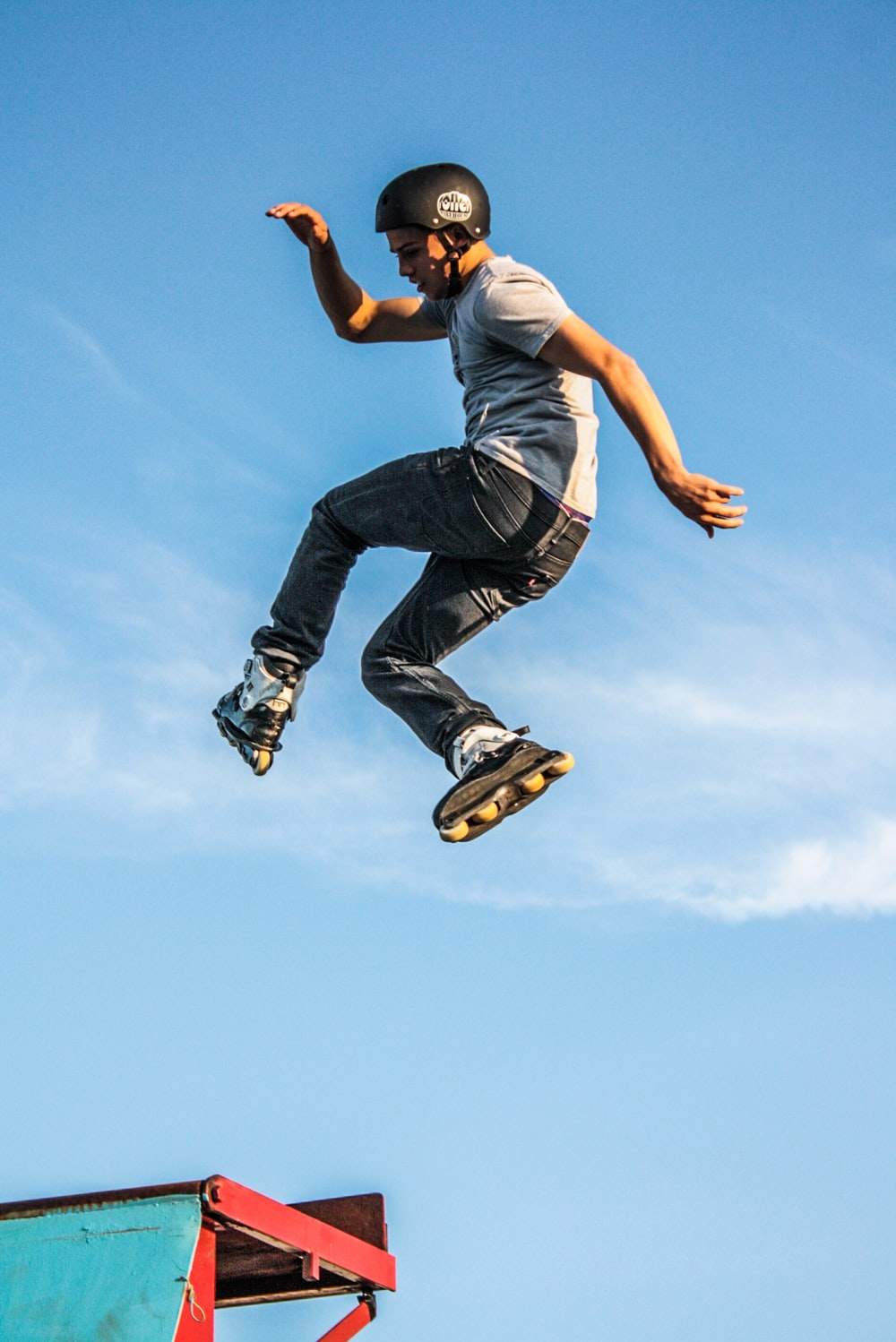 man in white t-shirt doing a roller skate trick in air