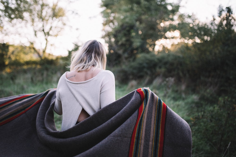 standing woman holding gray blanket surrounded by green grass