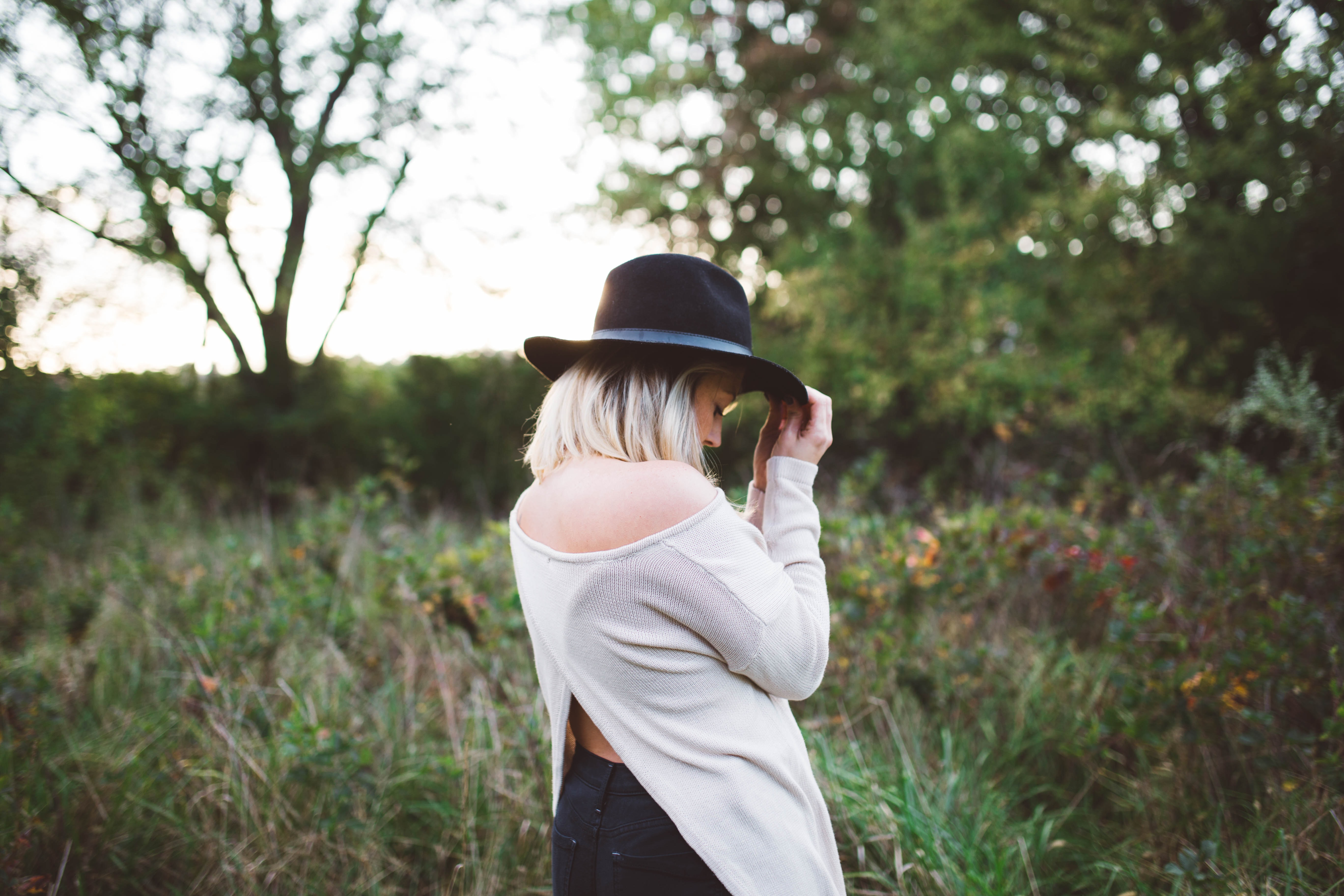 woman in white off shoulder long sleeved top holding black hat