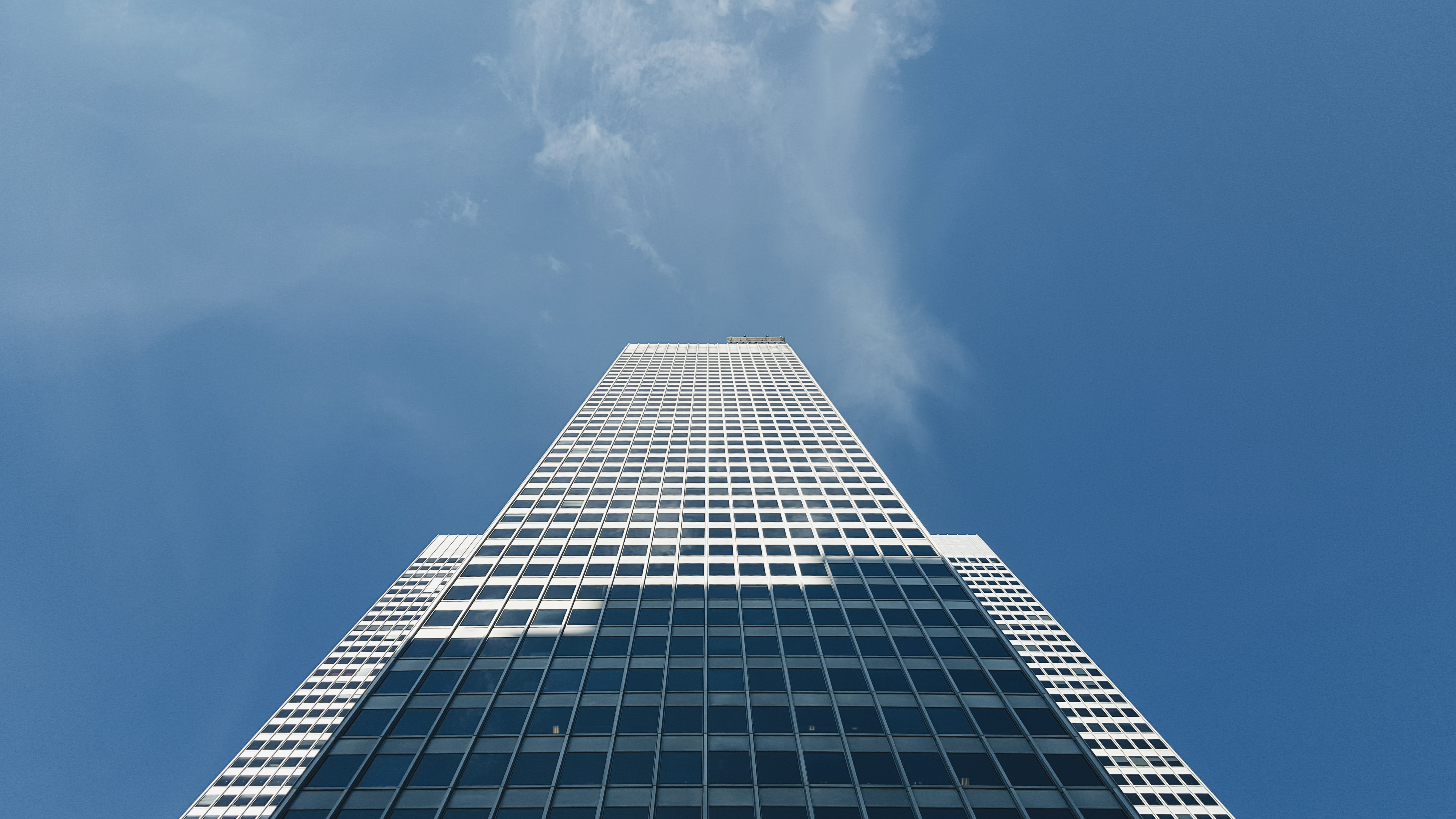The white exterior of a tall skyscraper under a blue sky