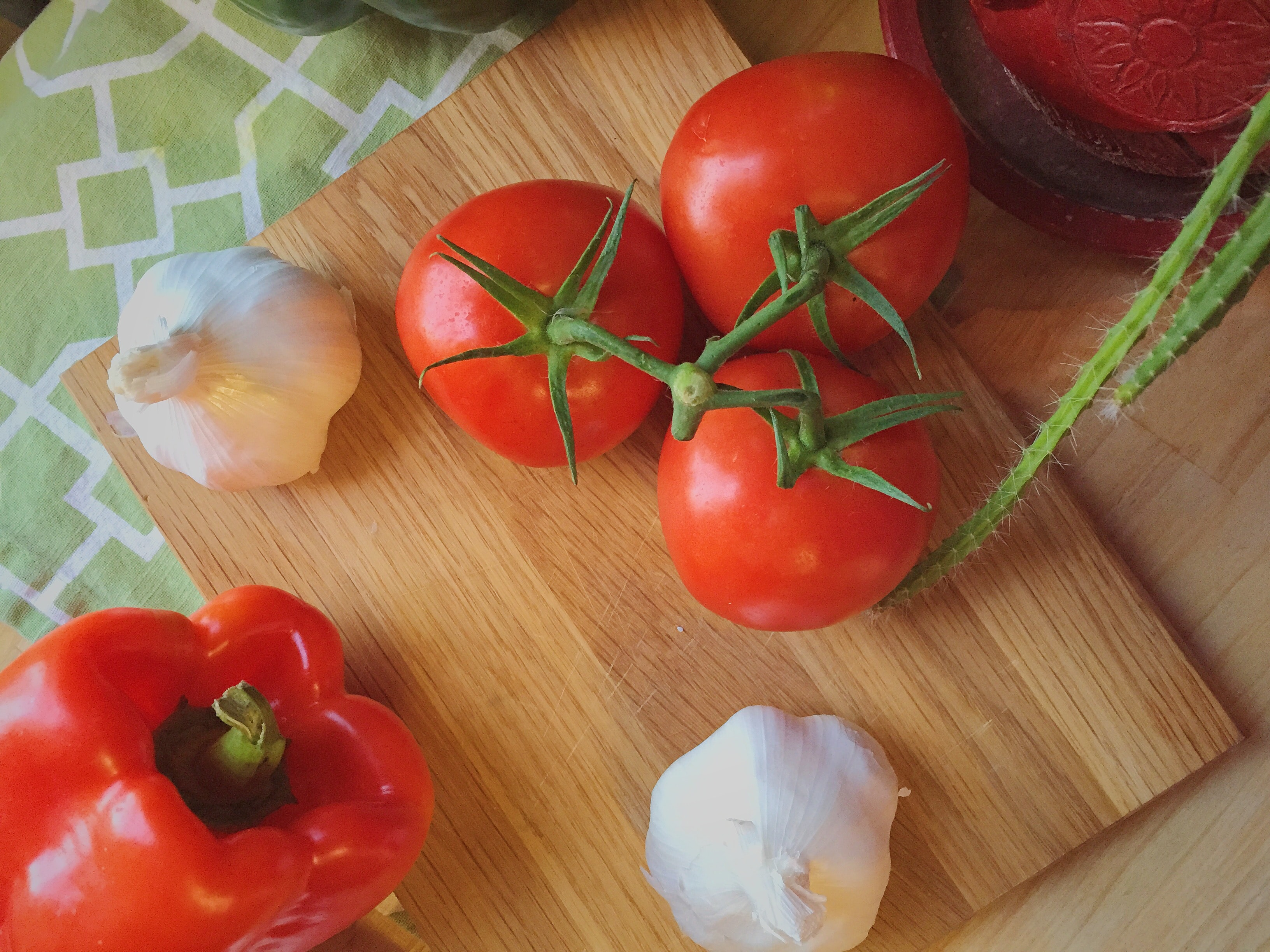 Fresh tomatoes, garlic, and peppers on a cutting board