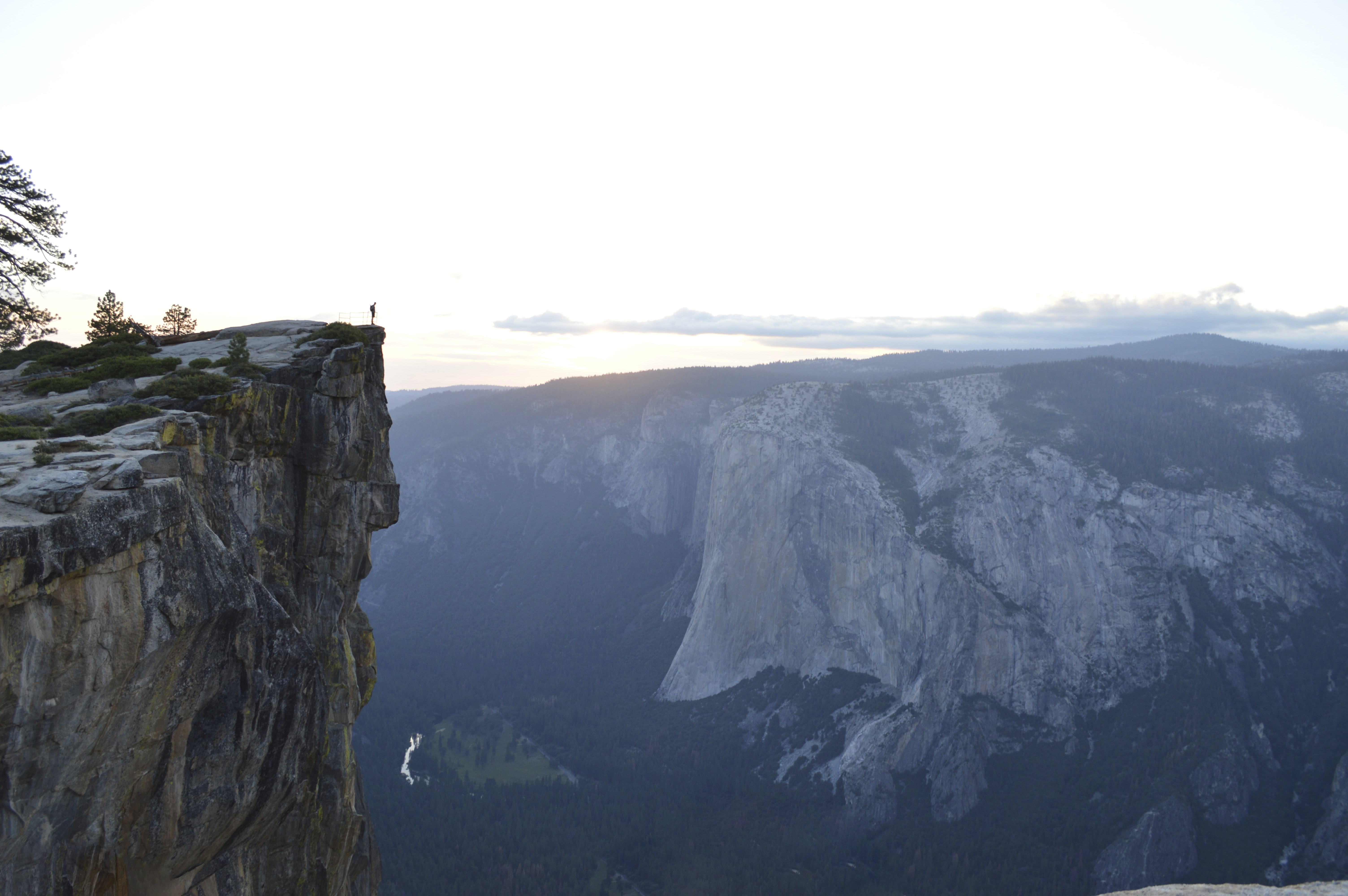 A silhouette of a man standing on a rocky ledge and looking into the breathtaking Yosemite Valley