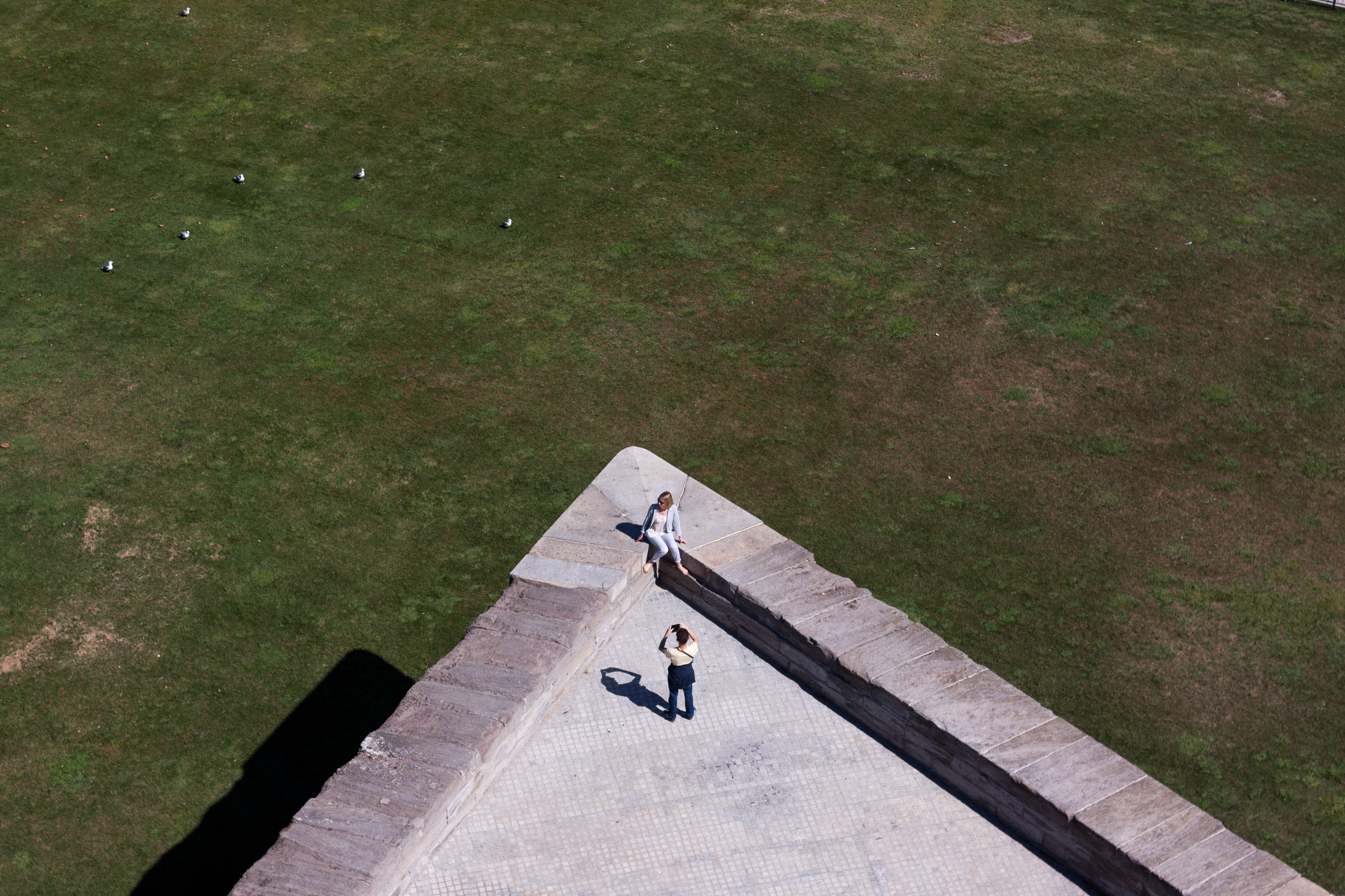 aerial photo of two person taking photo on top of building