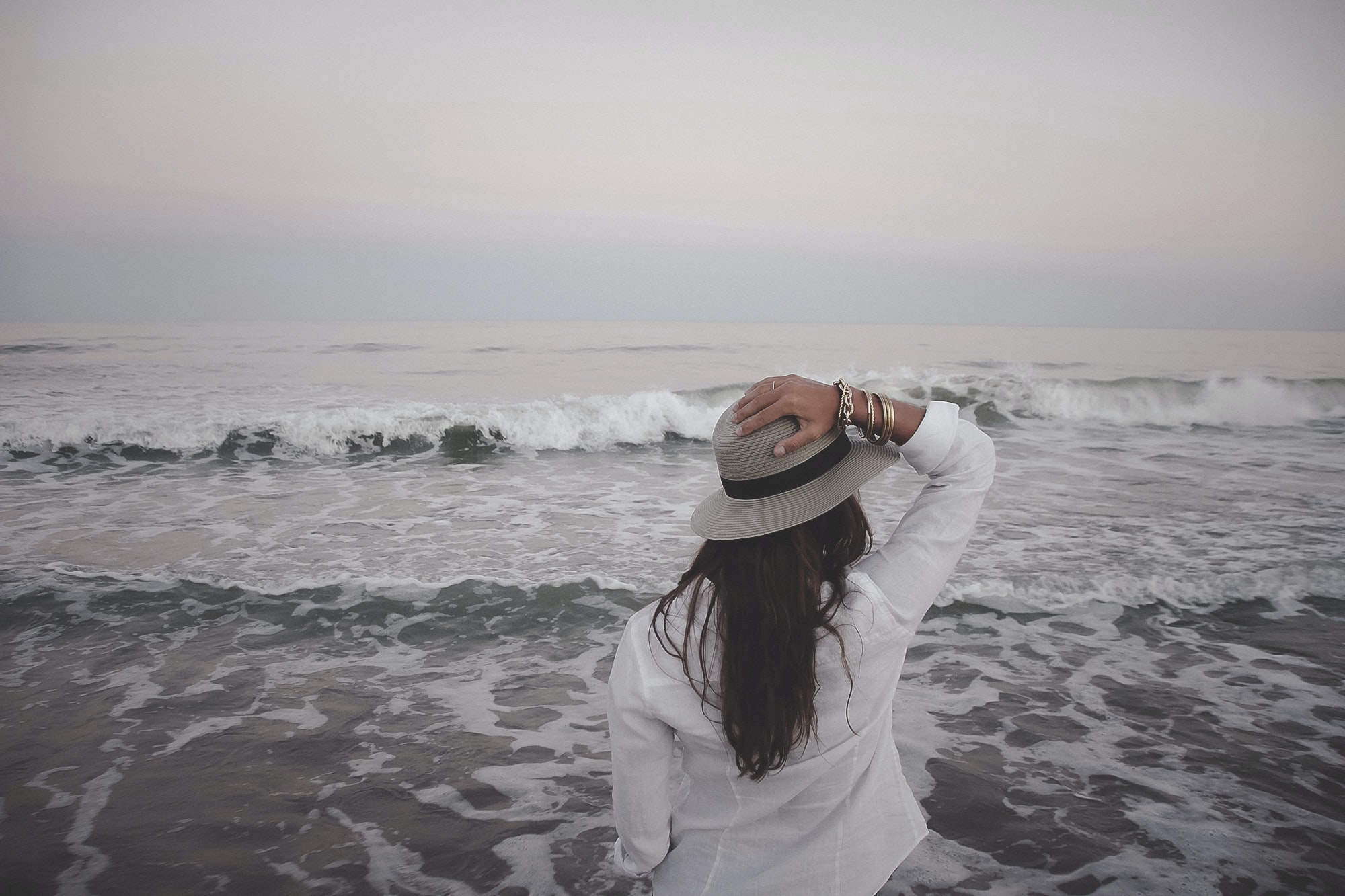 Woman in white shirt holding hand on a hat watching the ocean waves on a cloudy day