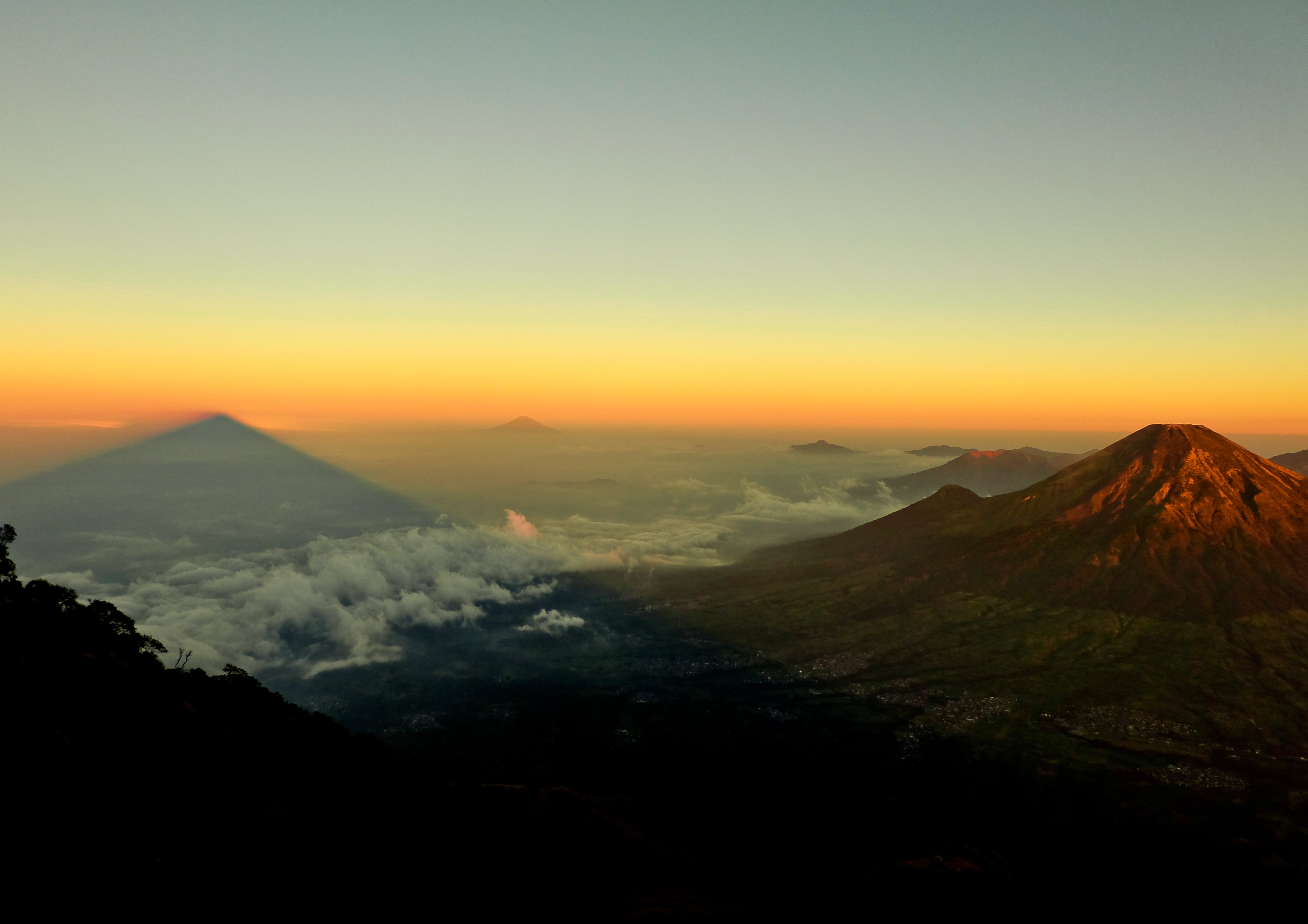 A volcano towering above a vast cloud-covered plain during sunset
