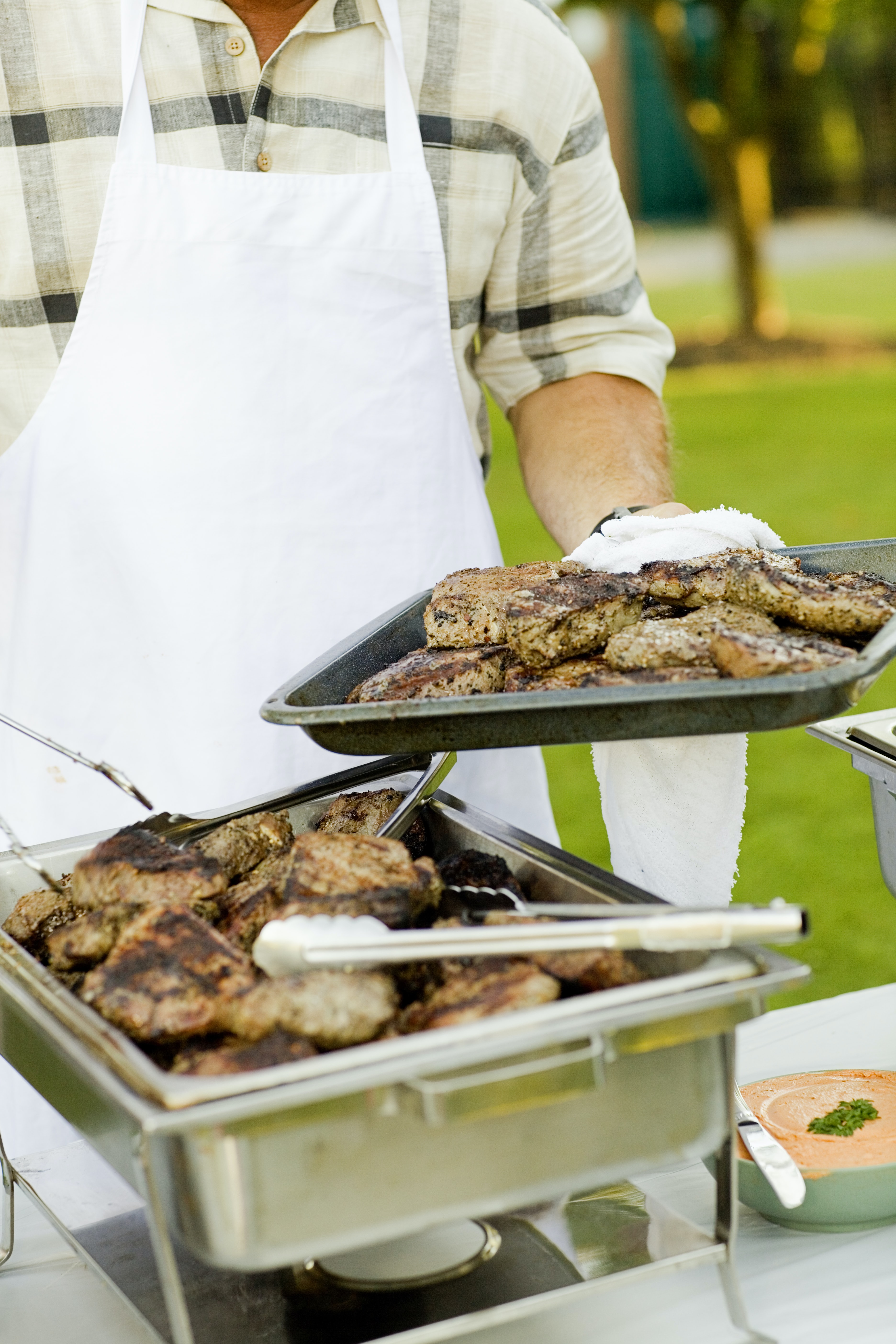 A man wearing a white apron setting up a catering table of BBQ food