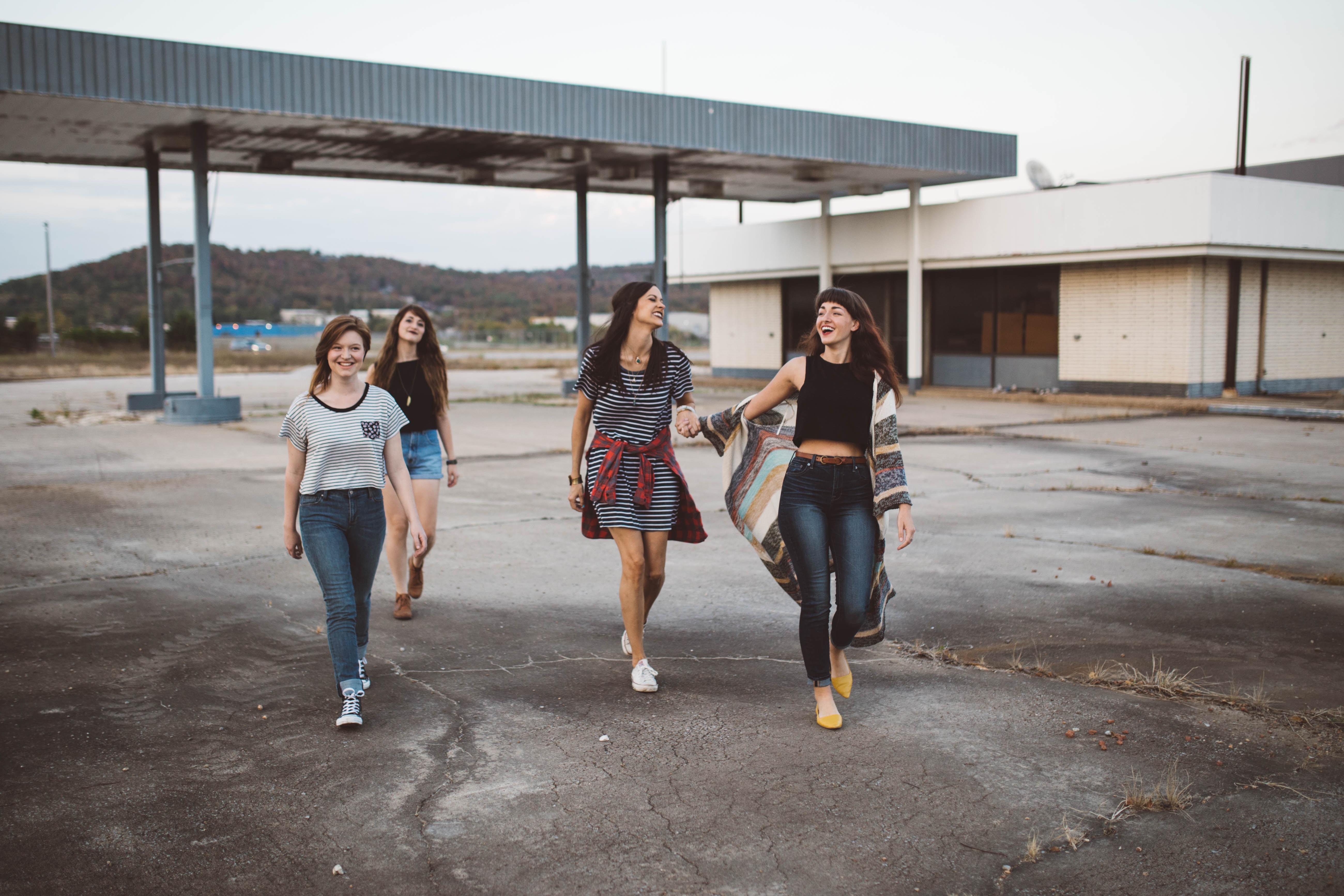 four girls walking near warehouse during daytime