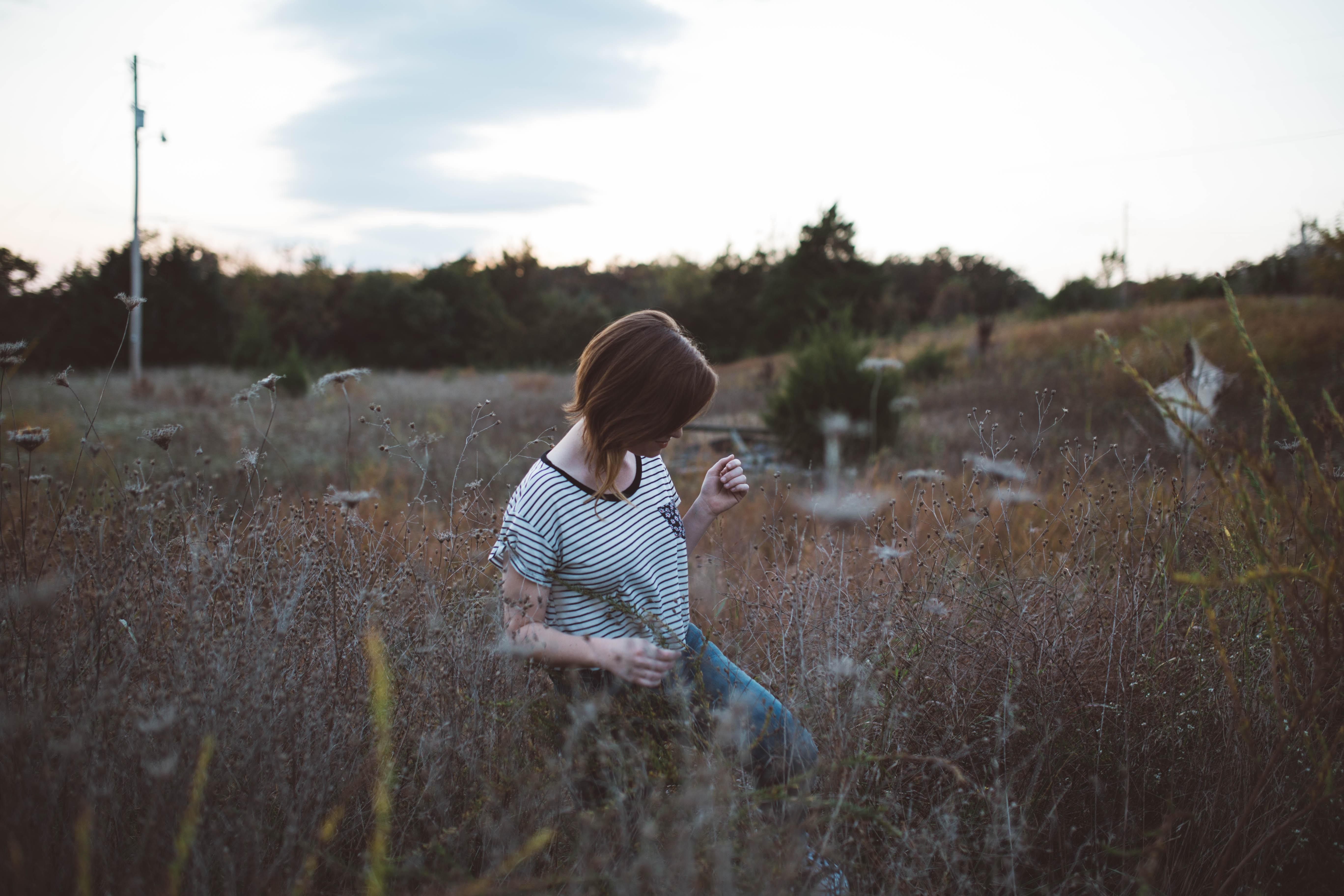 woman walking on brown leaf plant at daytie