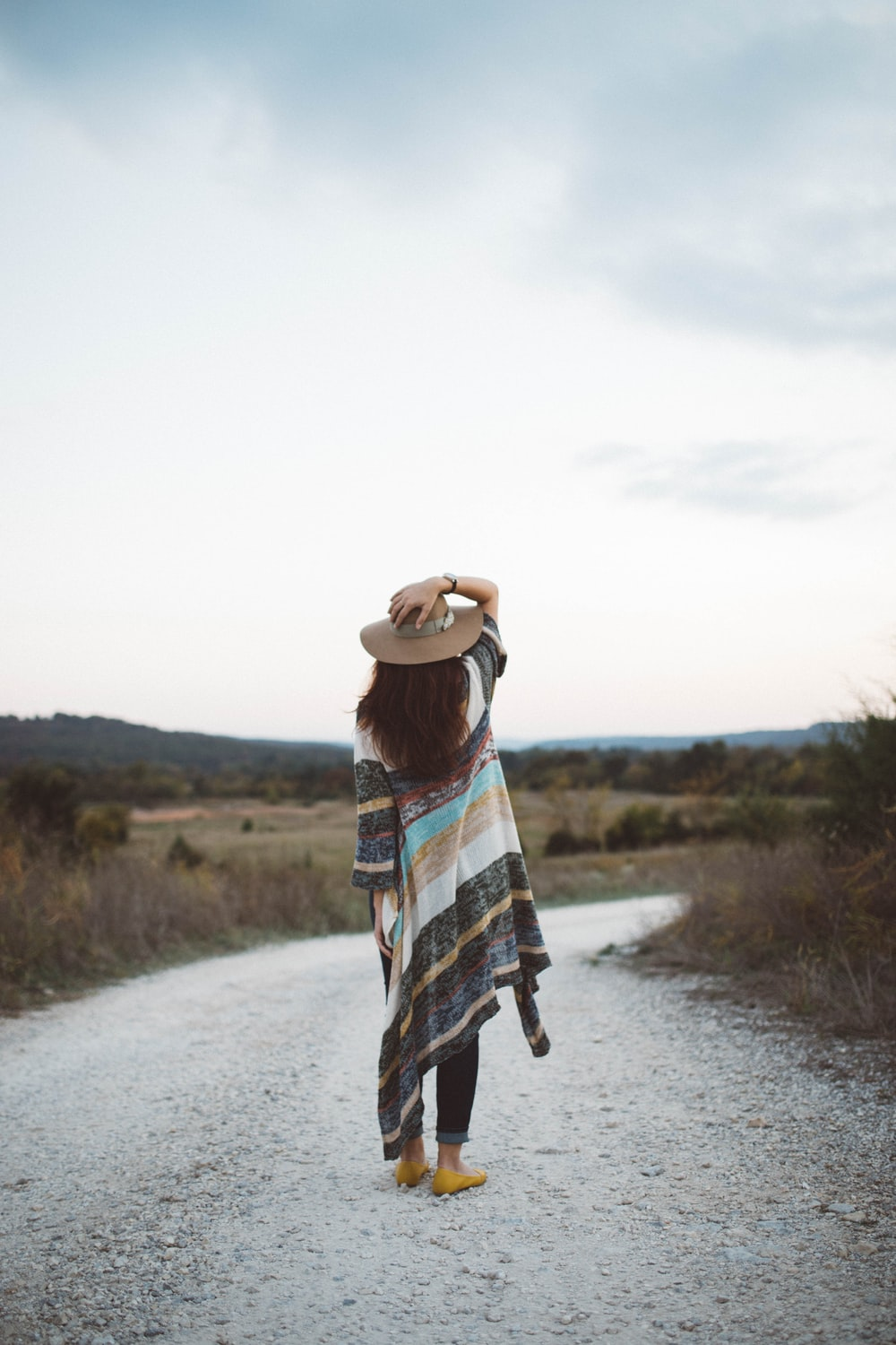 standing woman holding her hat at the middle of the road during day