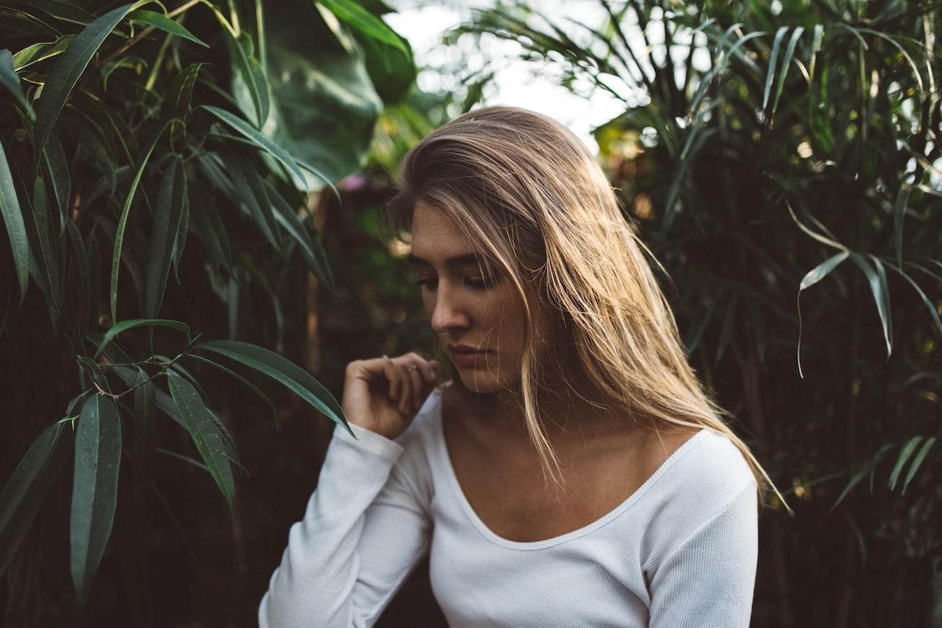 Blonde Frau mit weißem Shirt vor grünen Pflanzen