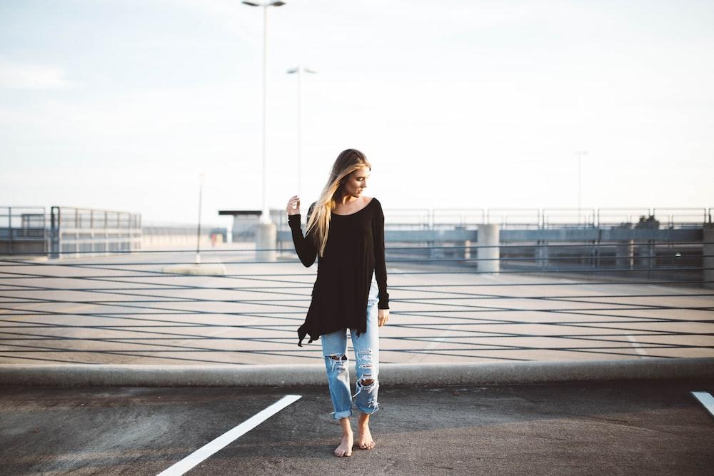 woman standing on gray concrete pavement