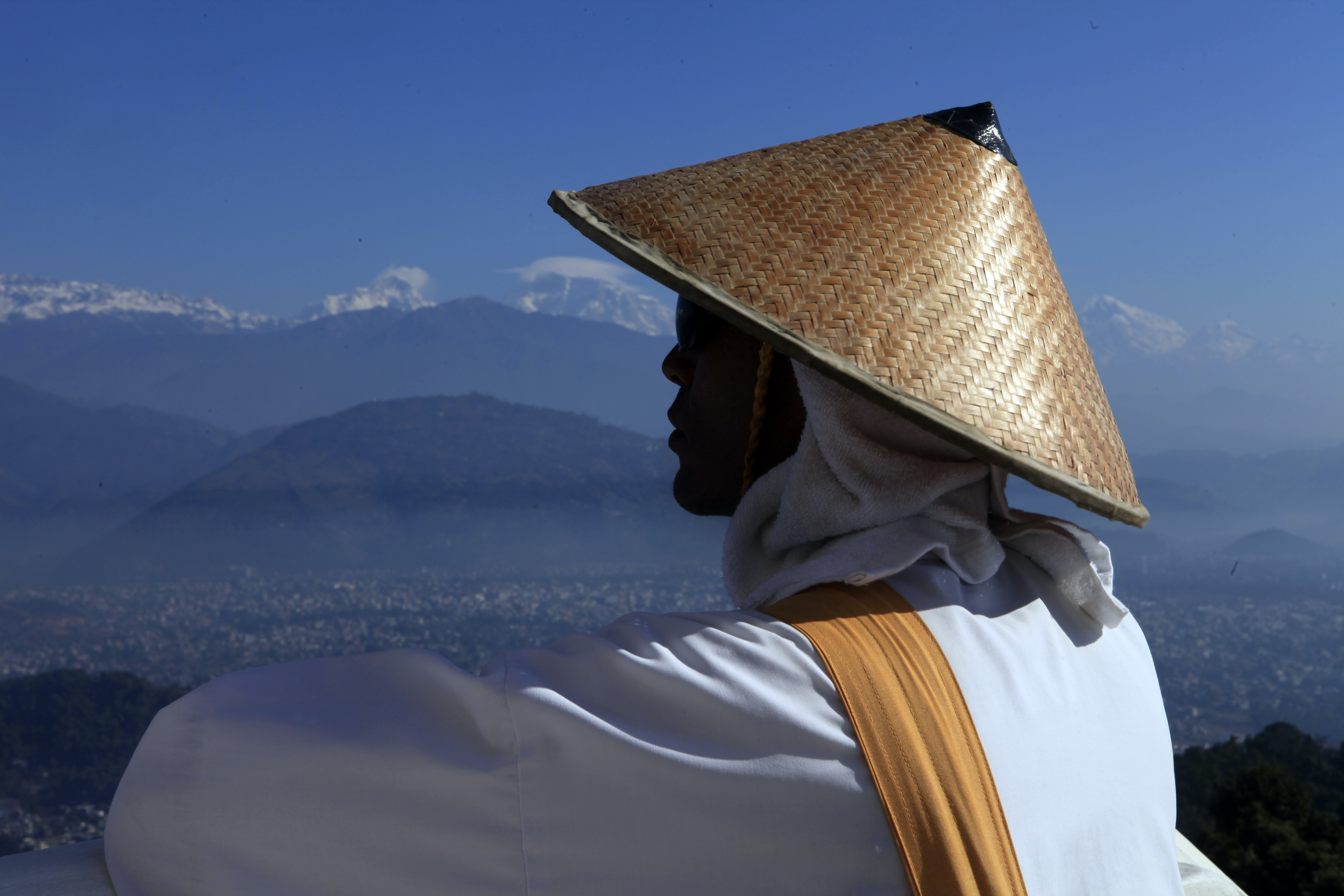 Person in a robe and Asian conical hat looking out at mountains