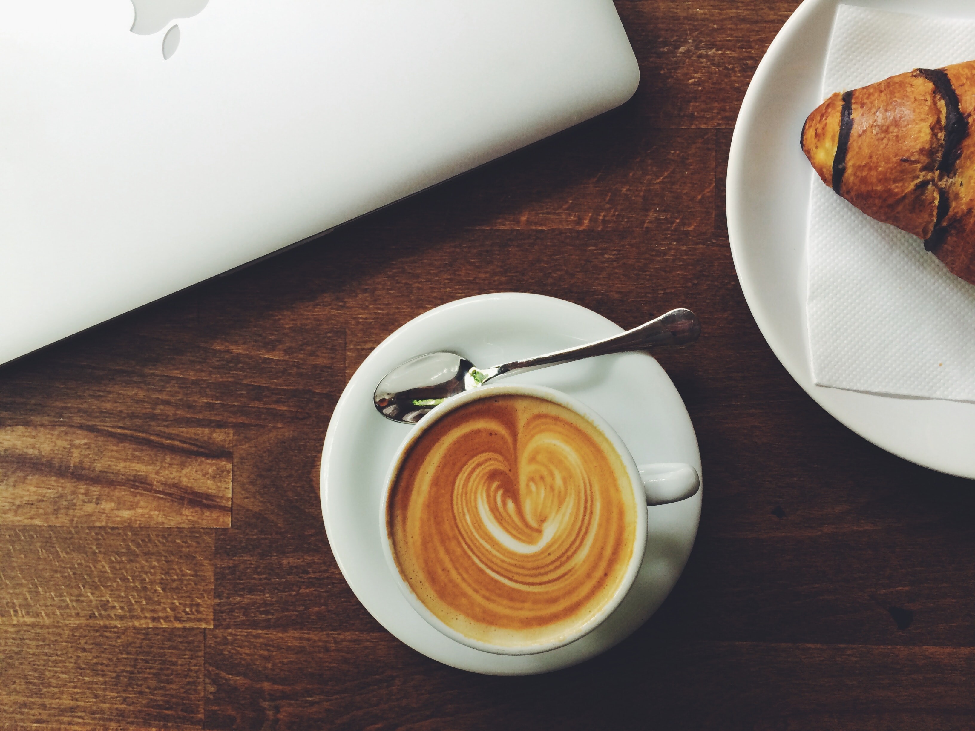 An overhead shot of a latte near a croissant and a MacBook