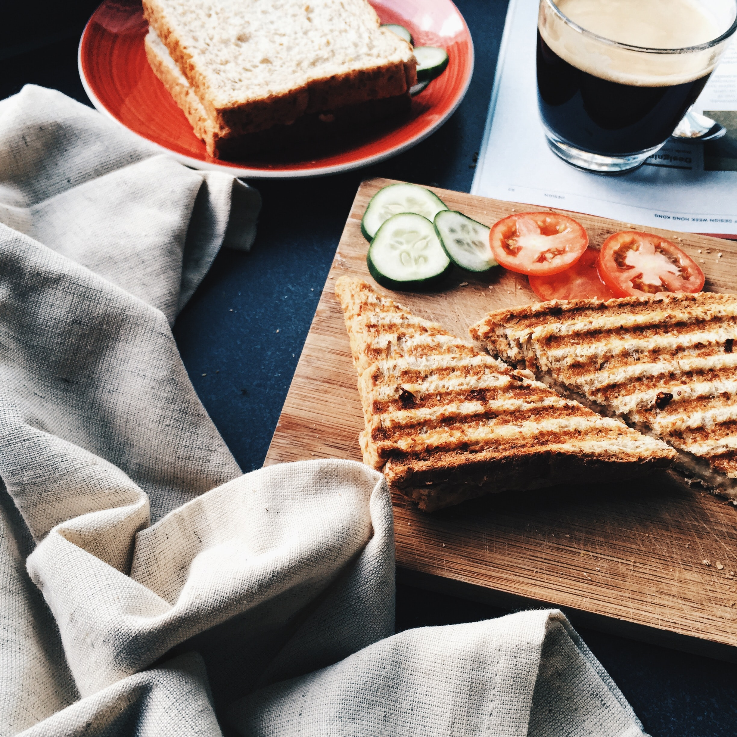 sliced grilled bread beside tomatoes and cucumbers on brown wooden board