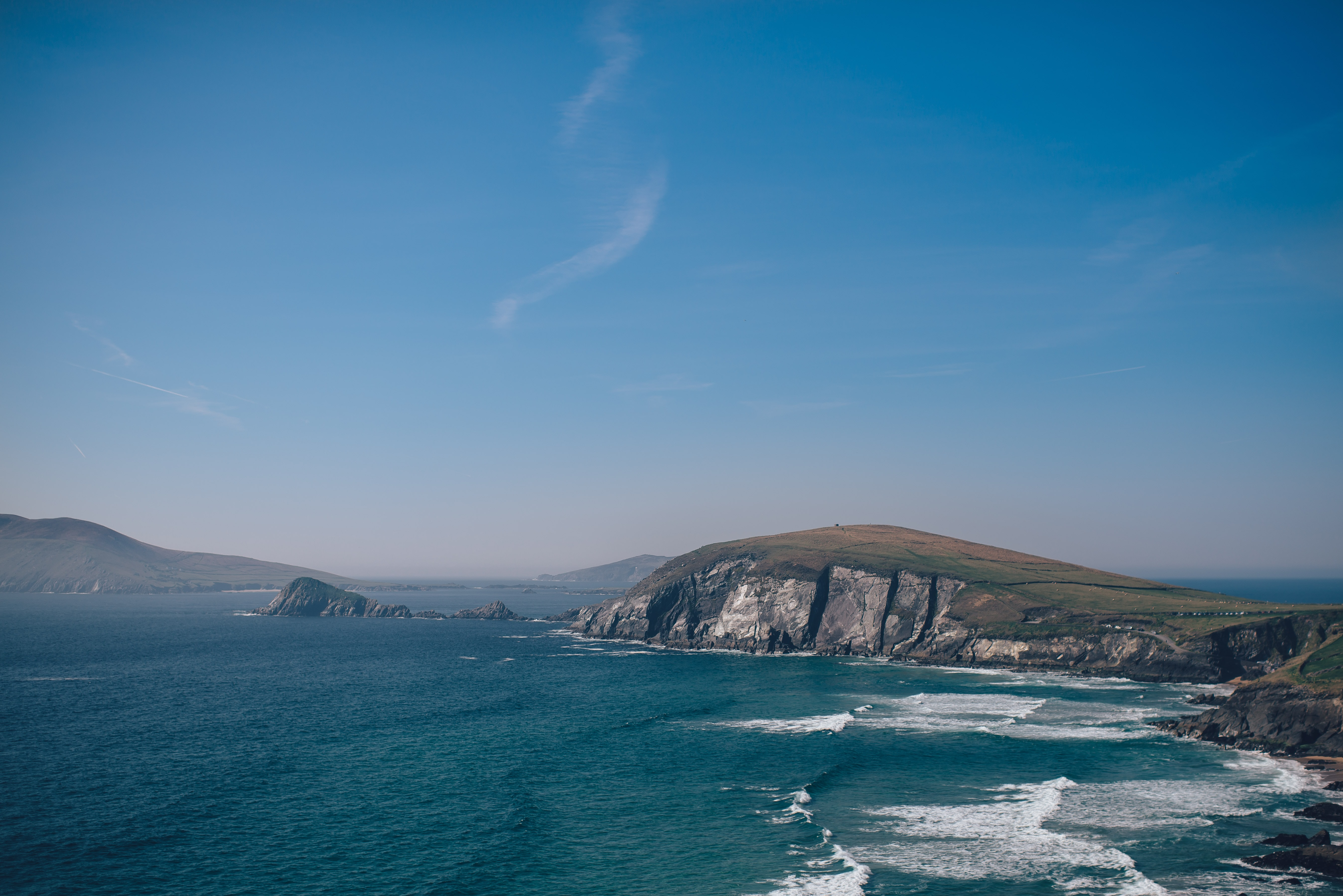 sea waves beside gray and green cliff under clear blue sky during daytime