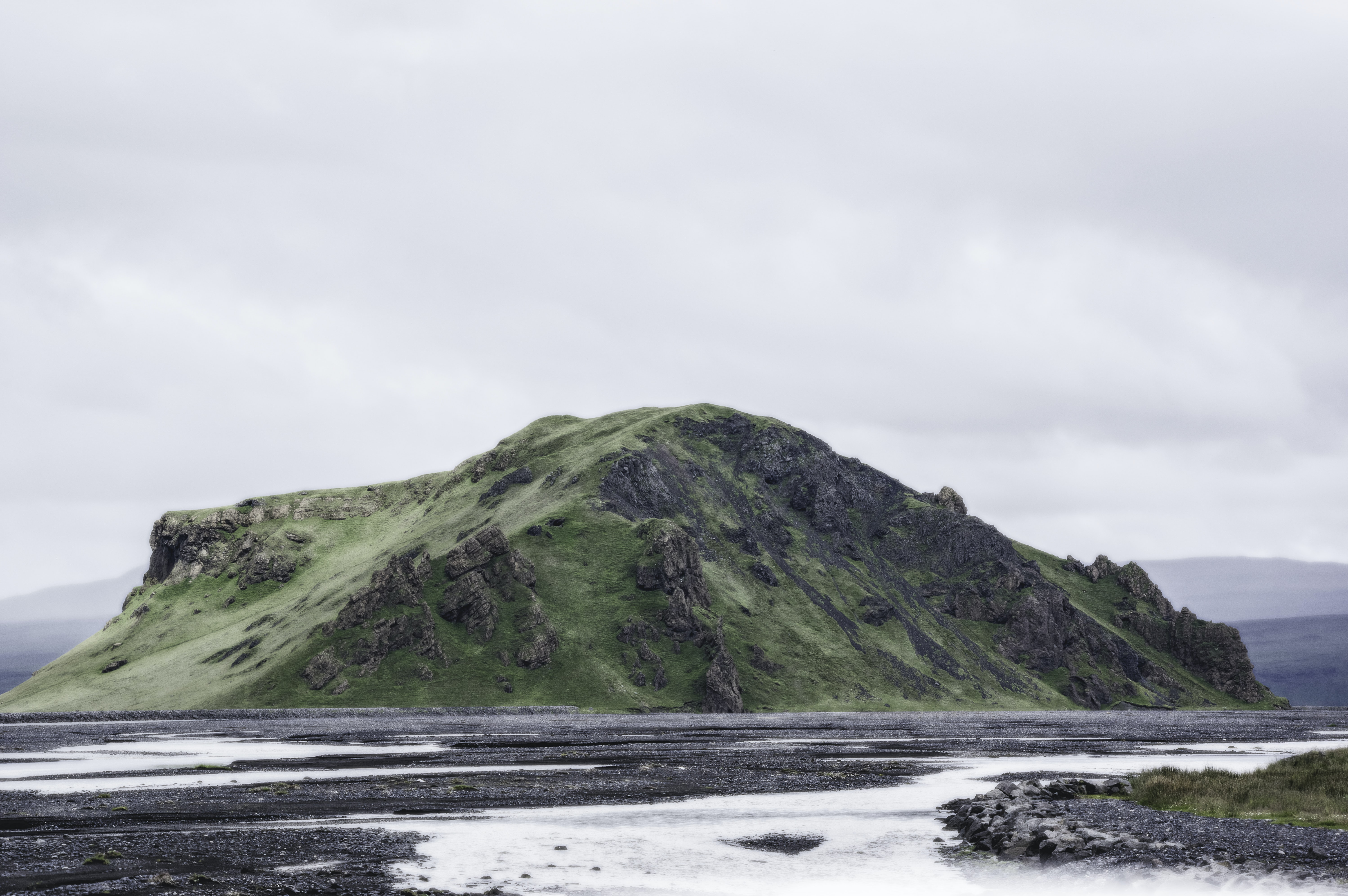 A rugged green hillock in the middle of an icy field in Iceland