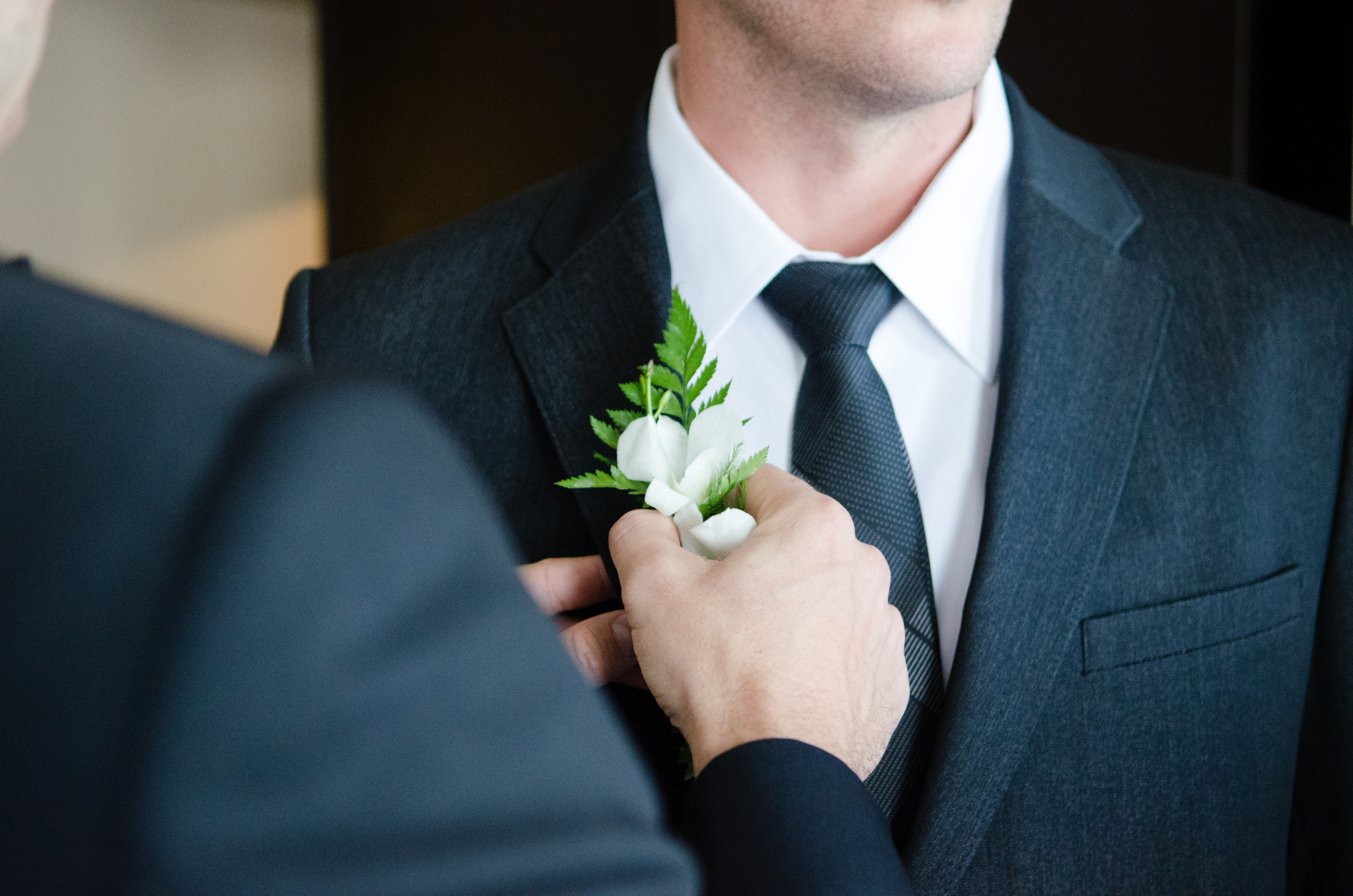A groomsman in a suit pins a boutonniere on the groom, who wears a black tie