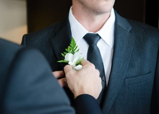 man attaching flower on another man's lapel in a well-lit room